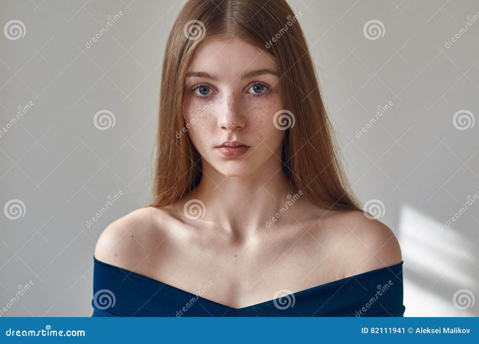 Skönhettema: stående av en härlig ung flicka med fräknar på henne framsida och bära en blå klänning på en vit bakgrund i studi