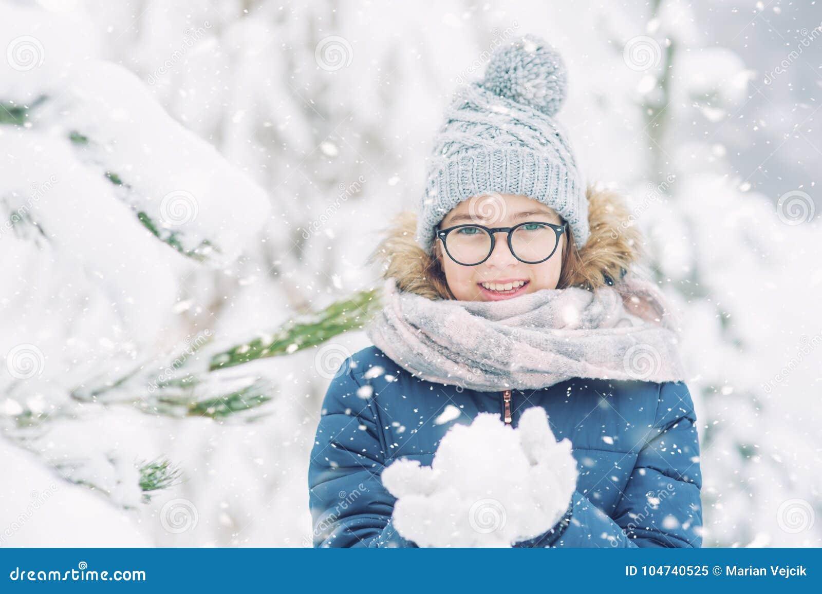 Skönhetvinterflickan som blåser insnöad frostig vinter, parkerar eller utomhus-