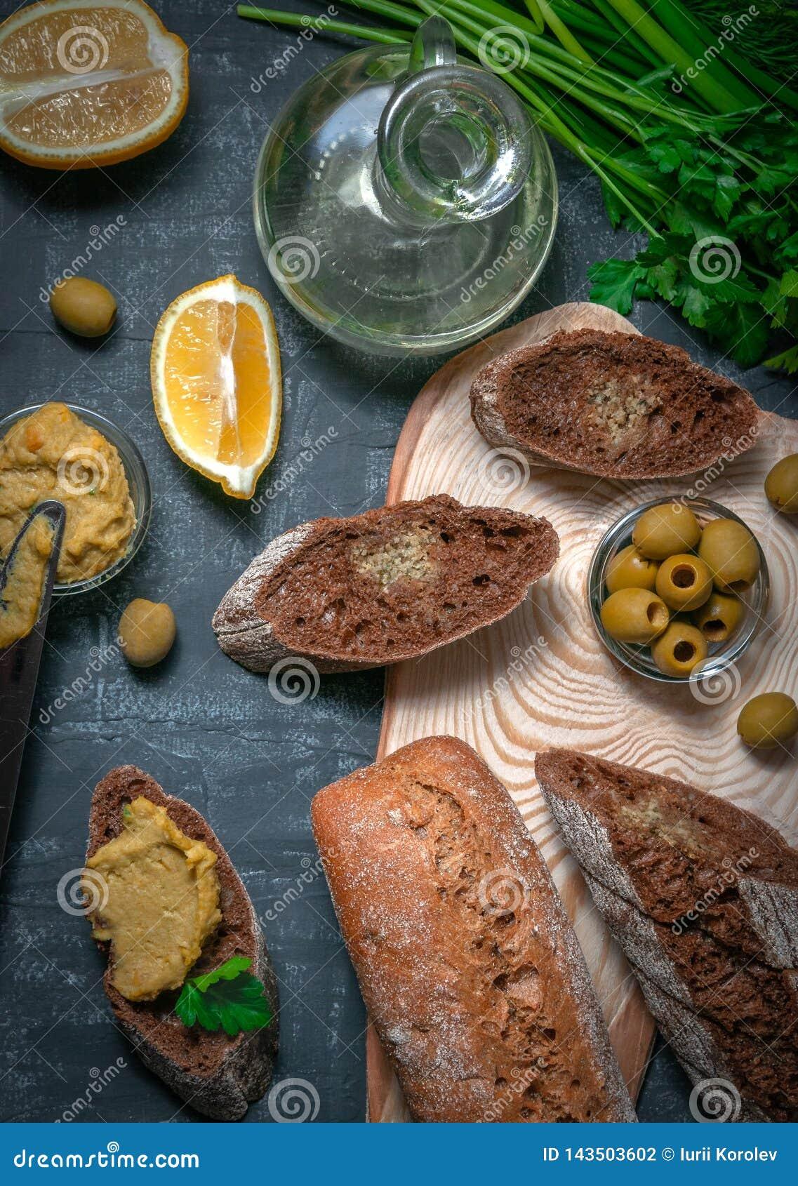 Skład dwa baguettes otręby i cała zbożowa mąka Kanapka hummus i oliwki Naczynie z jarzynowym olejem Na a