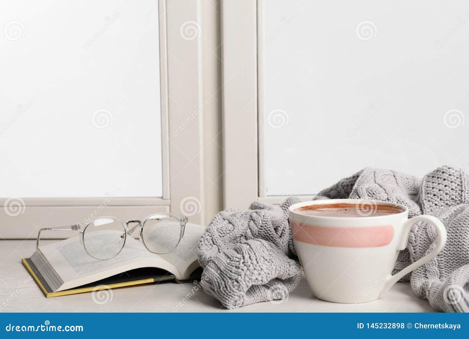 Skład z filiżanką gorąca czekolada i książka na windowsill, przestrzeń dla teksta