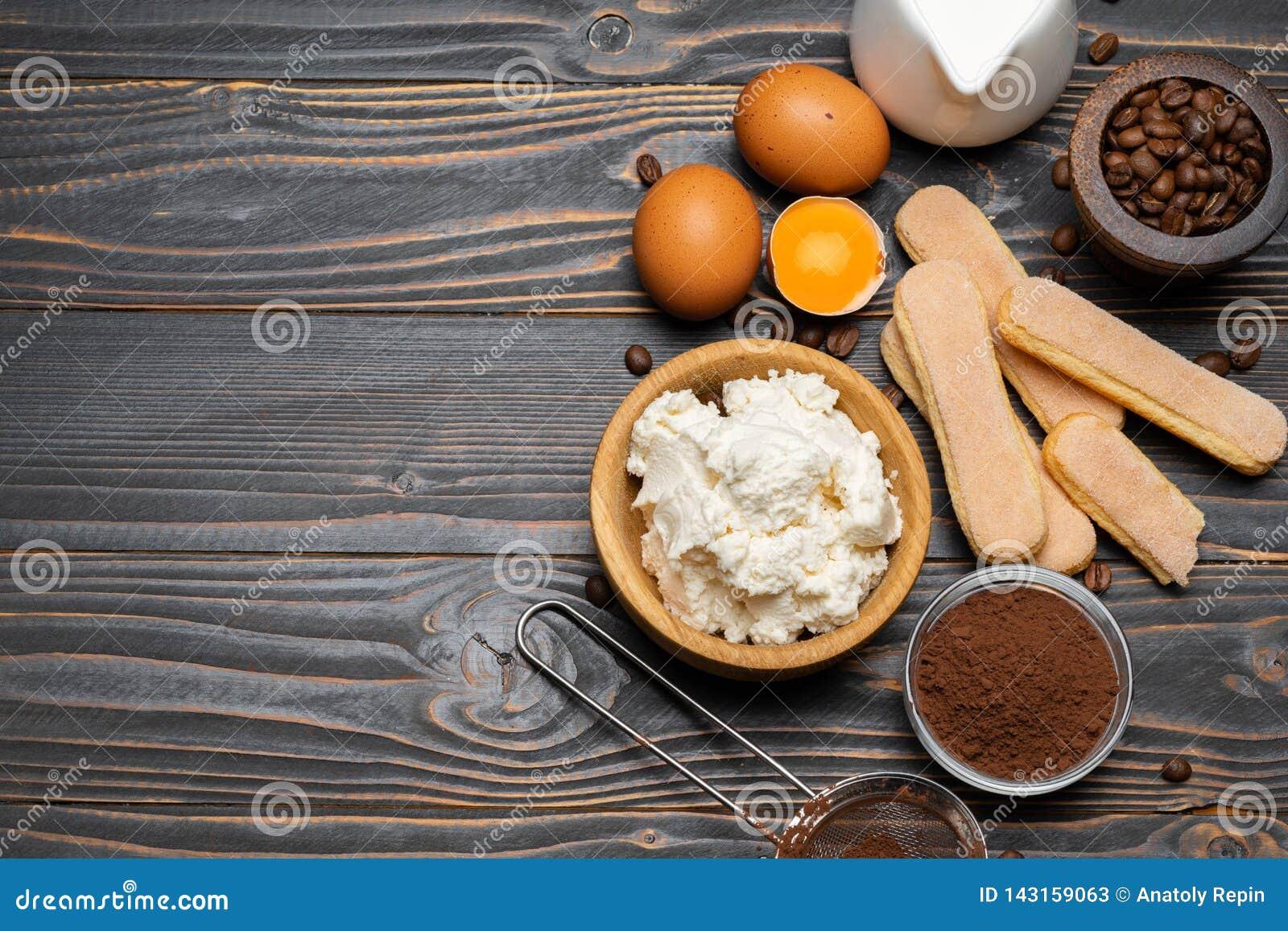 Składniki dla kulinarnego tiramisu Savoiardi biskwitowi ciastka, mascarpone, ser, cukier, kakao, kawa i jajko -,