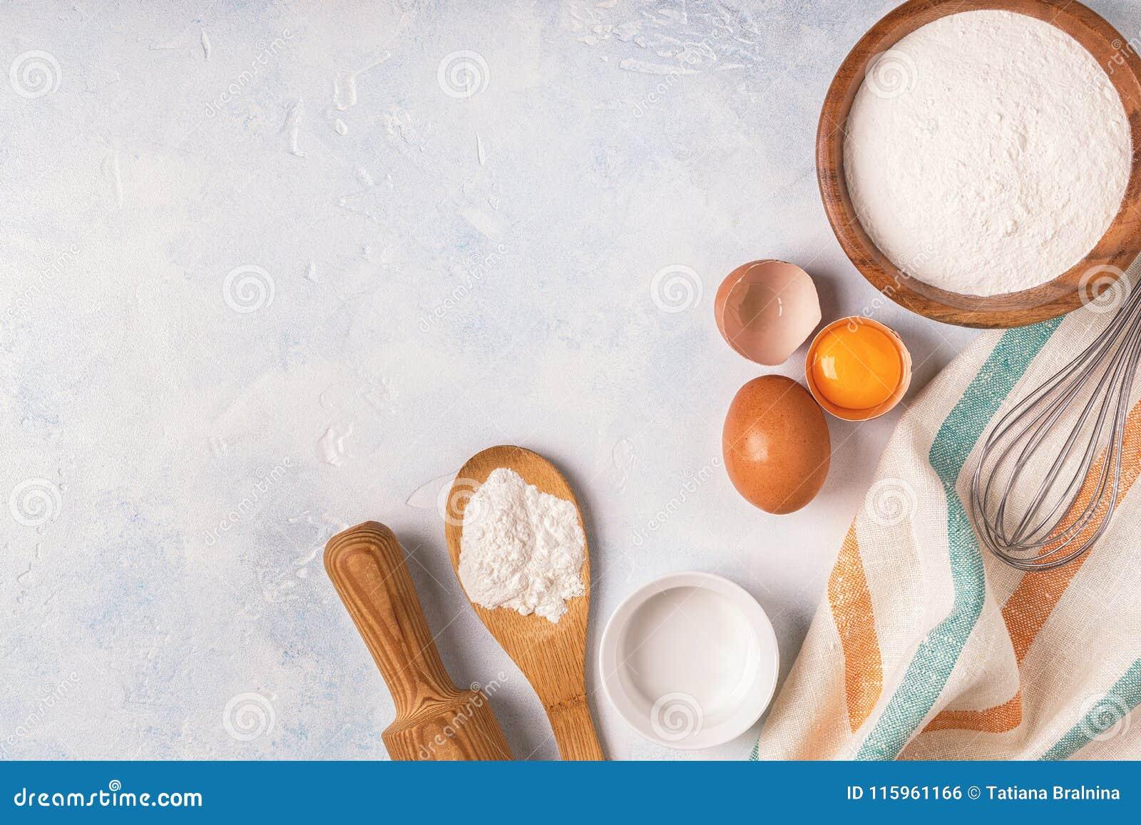 Składniki dla piec - mąka, drewniana łyżka, jajka