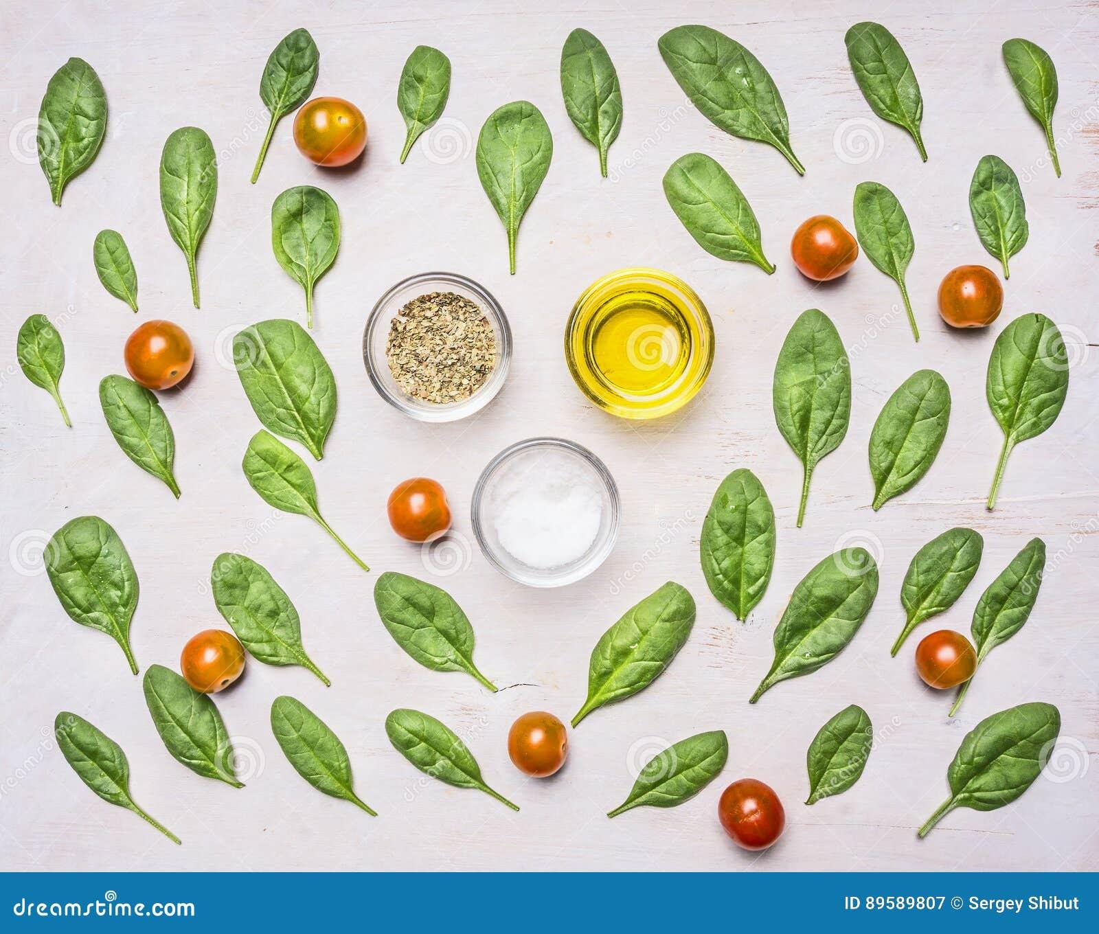 Składniki dla sałatki, ziele, oleju, pieprzu, soli i seasonings, na białym nieociosanym tle