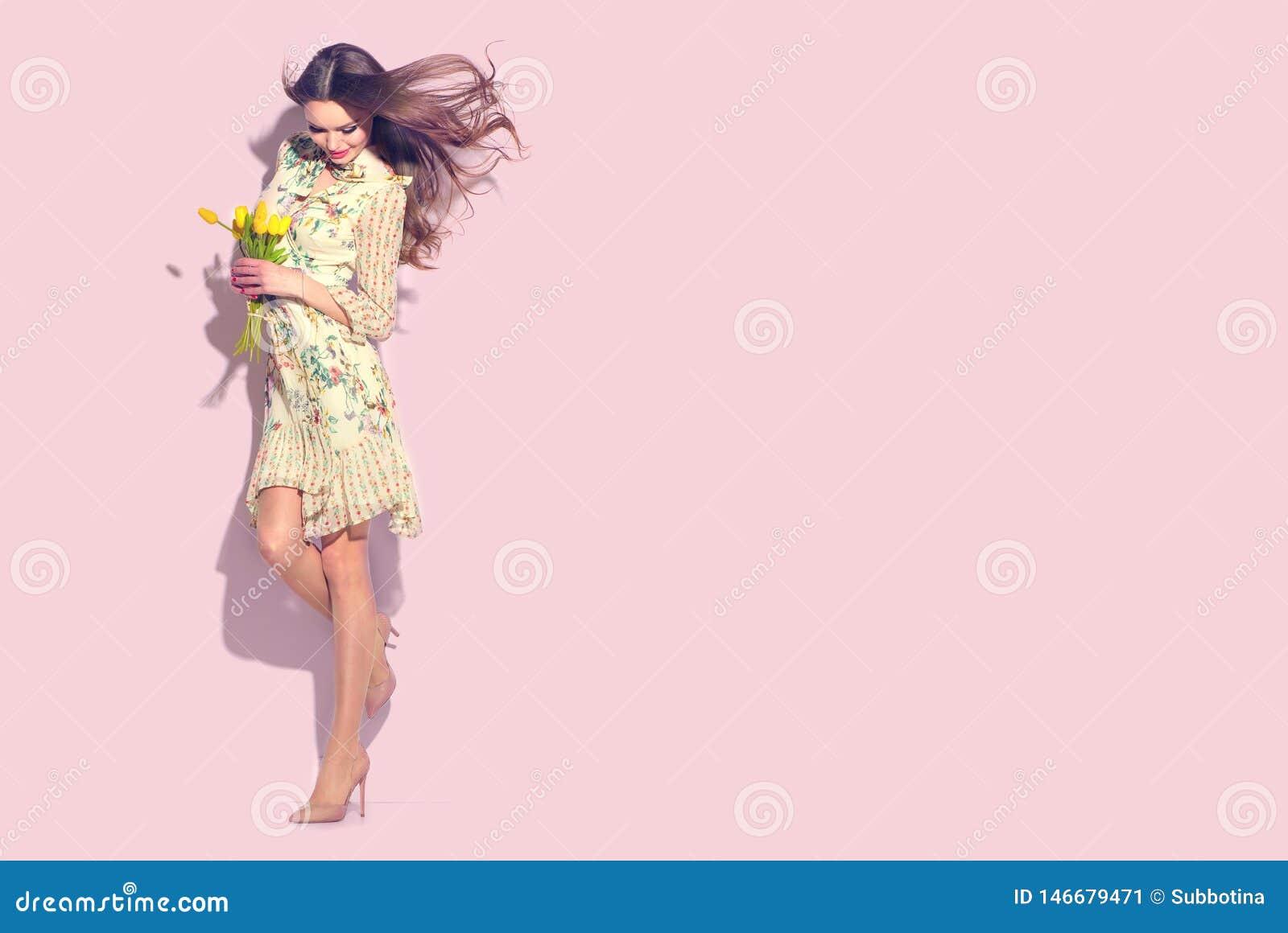Sk?nhetglamourflicka med v?rtulpanblommor H?rlig ung kvinna som poserar med buketten av tulpan Modellera den b?rande chiffongkl?n