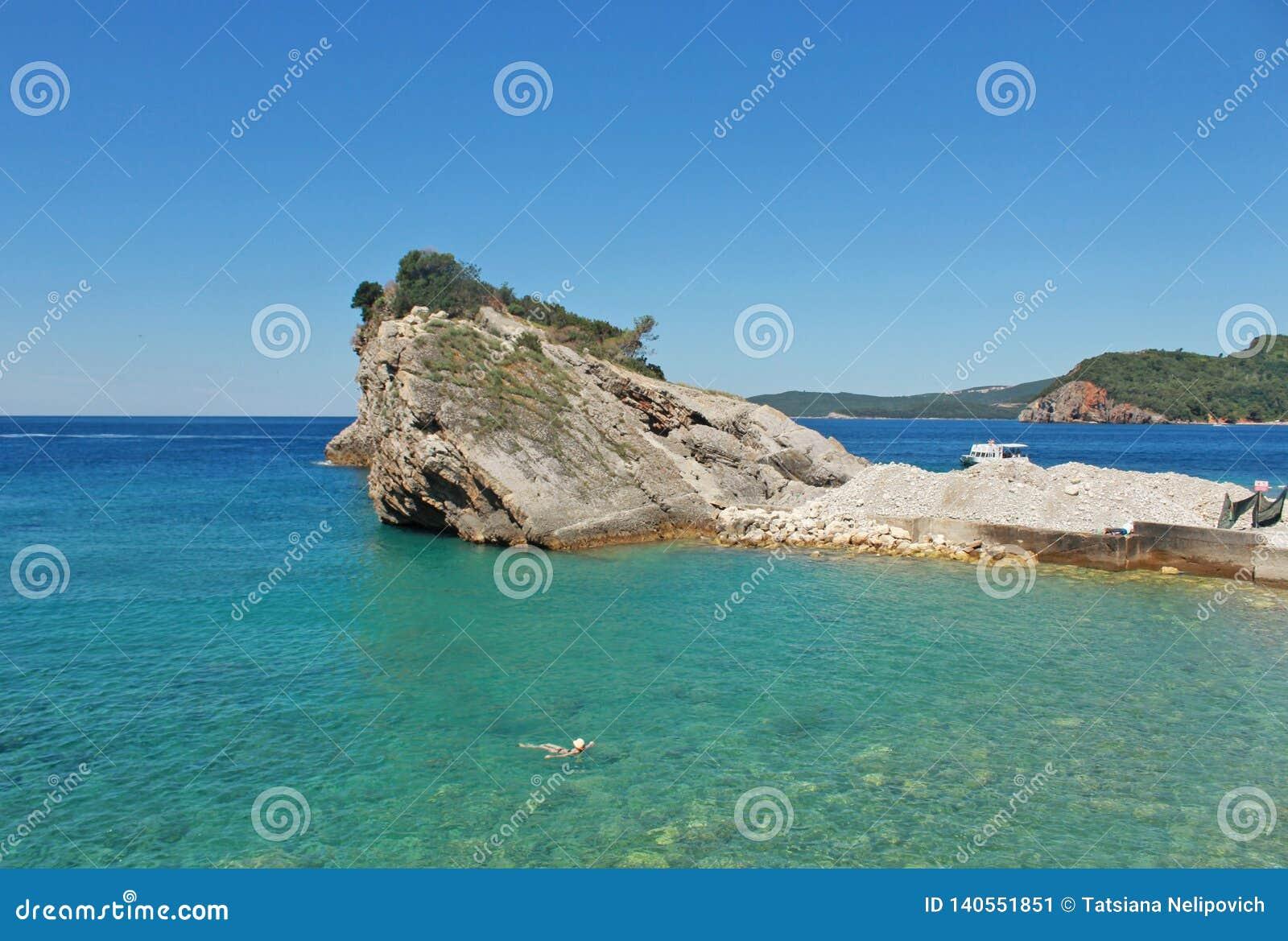 Skały i łódź na wyspie St Nicholas w Budva, Montenegro Raj plaża na wyspie w morzu Pojęcie podróż