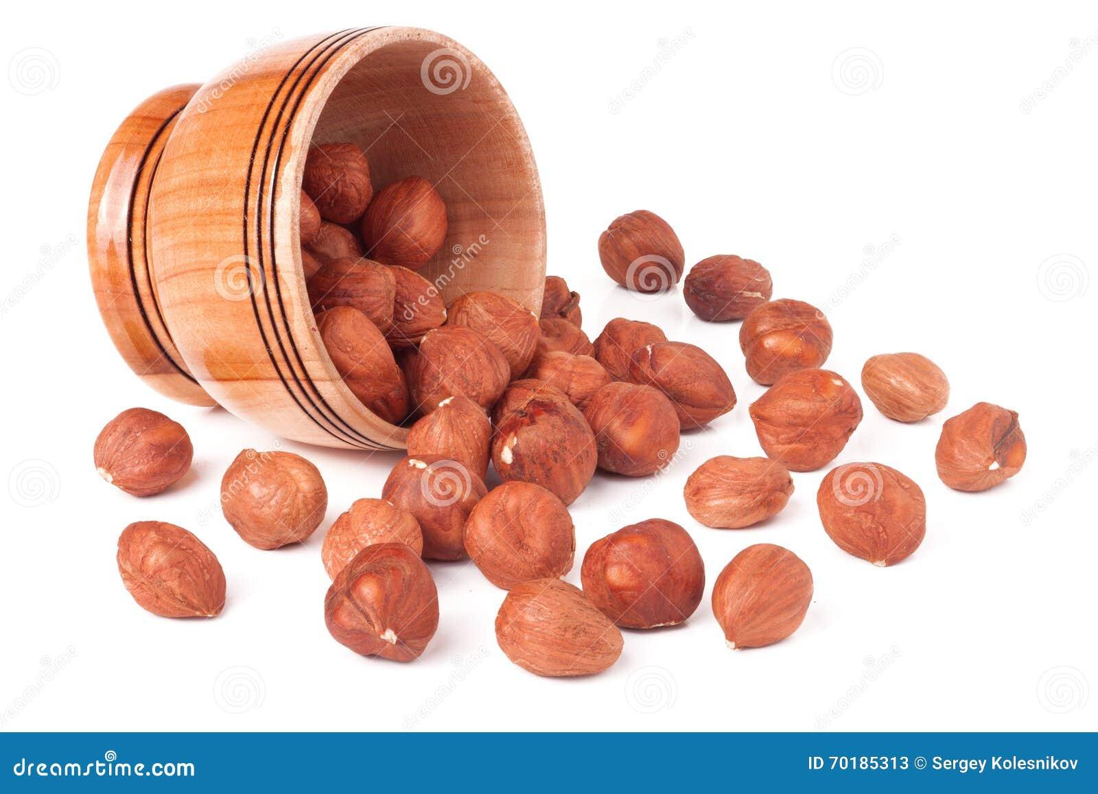 Skalade hasselnötter i en träbunke på vit bakgrund