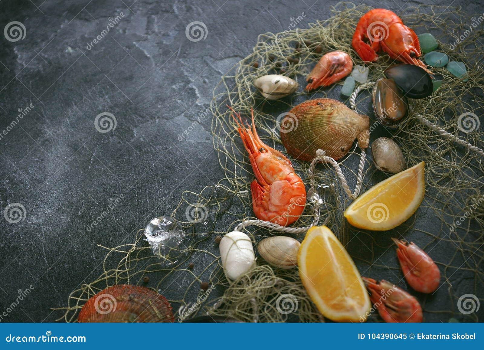 Skaldjur på en mörk bakgrund, räkor, musslor, musslor på den svarta stenen, kopieringsutrymme