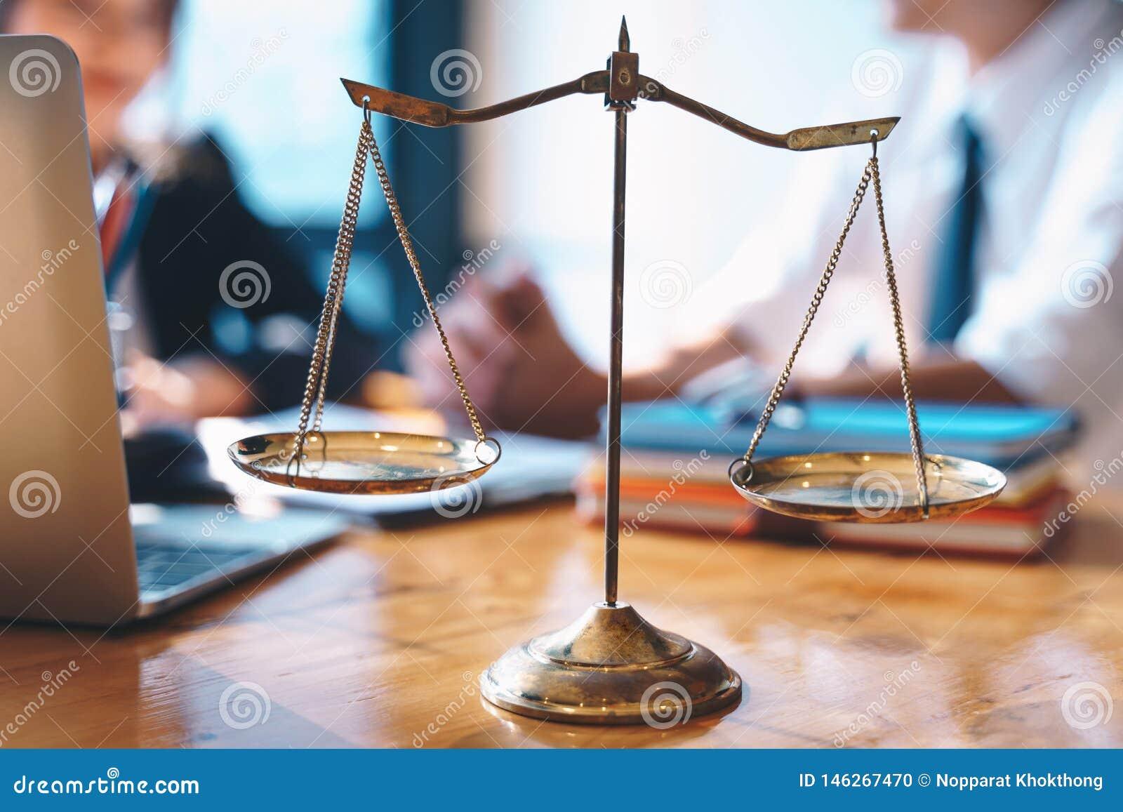Skalen von Gerechtigkeit auf Holztischhintergrund mit der Geschäftsfrau und männlichen Rechtsanwälten, die Vertragspapiere an den