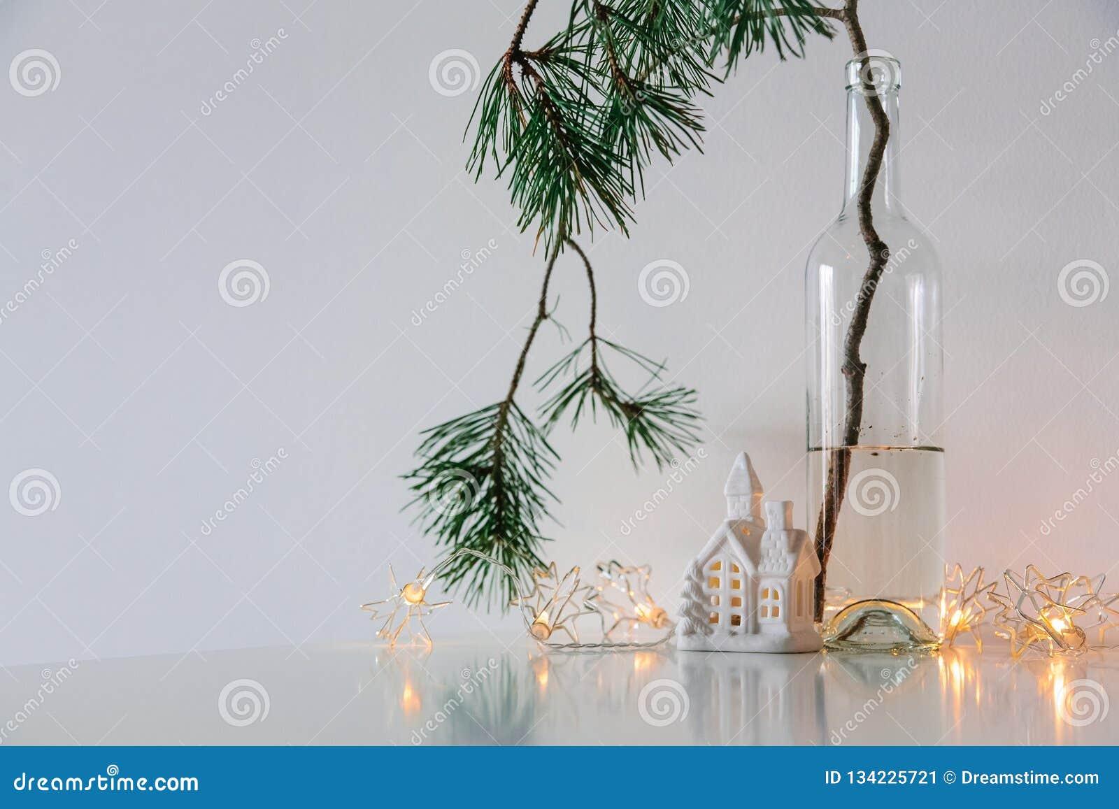 Skandinavischer Weihnachtsdekor Kiefernniederlassungen, Girlande und eine keramische Hauslampe