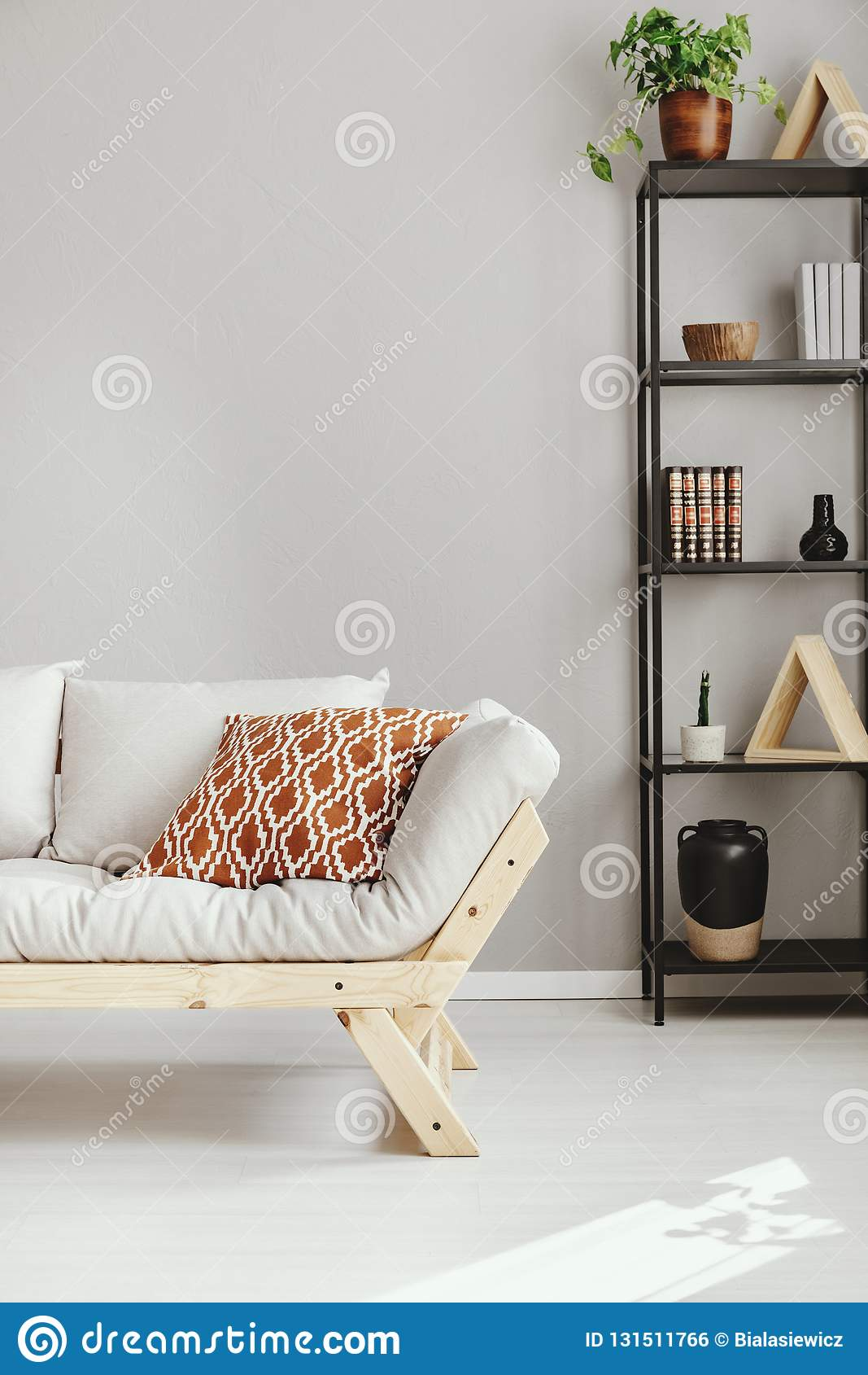 Skandinavisk soffa bredvid hylla med den olika sorten av tillbehör, verkligt foto med kopieringsutrymme