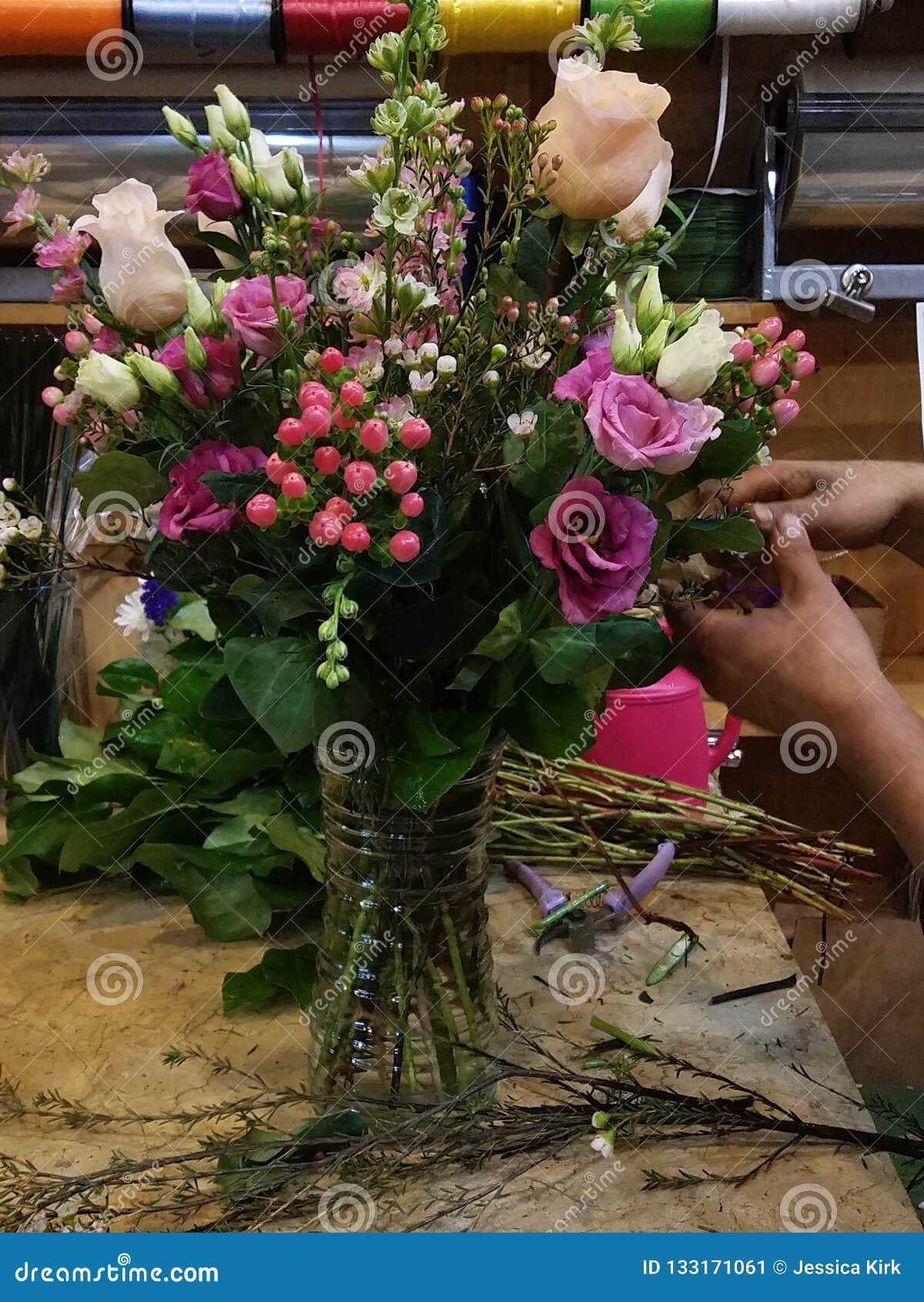 Skapa en blom- bukett med blandade rosa färger på blomsterhandeln Blomsterhandlarehänder som arbetar olik etnicitet