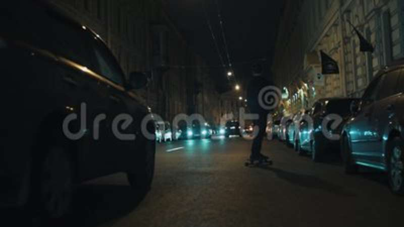 Skateboarder Guy In Black Hoodie Rides On Night City Driveway Stock