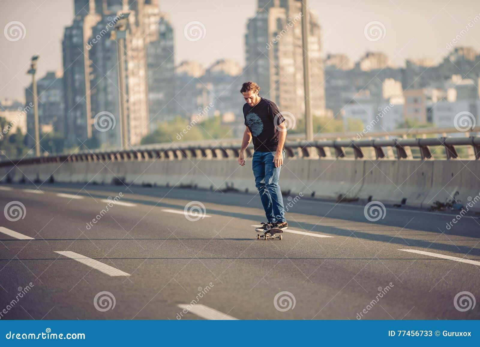 skateboarder riding a skate over a city road bridge free ride s