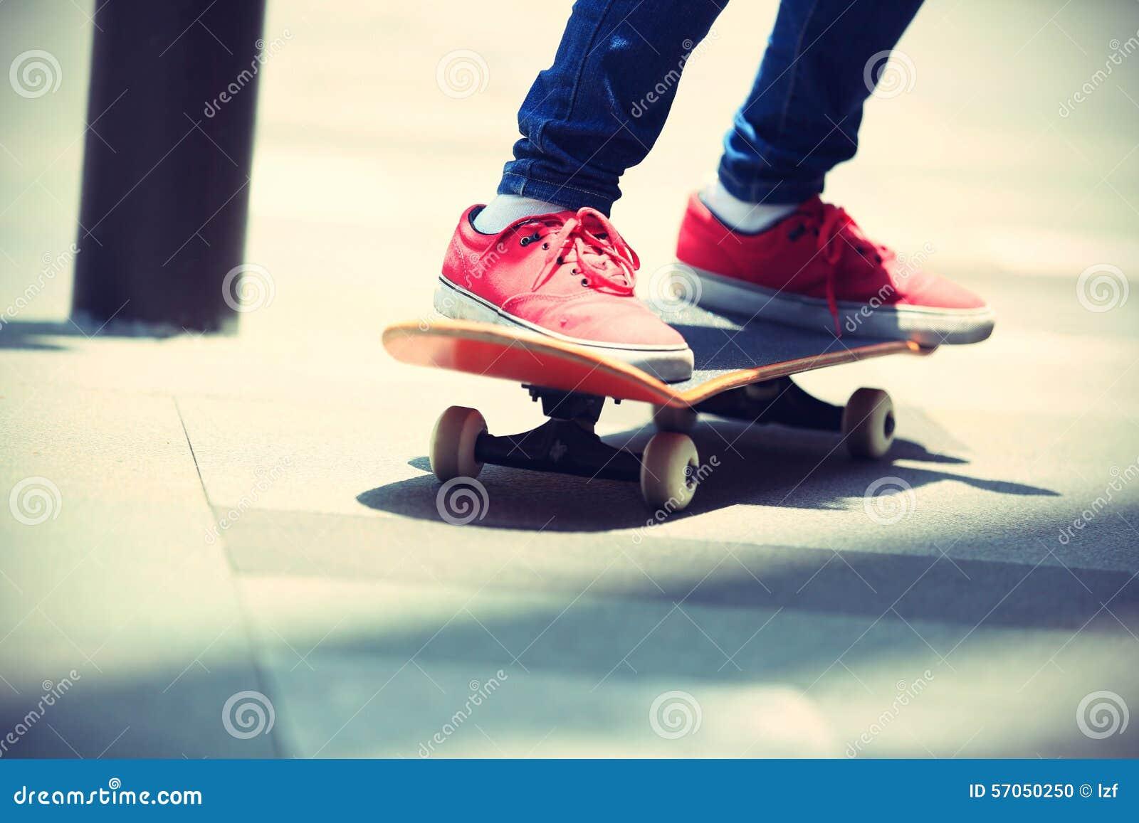Skateboarderbenen die op skateboard op stad berijden