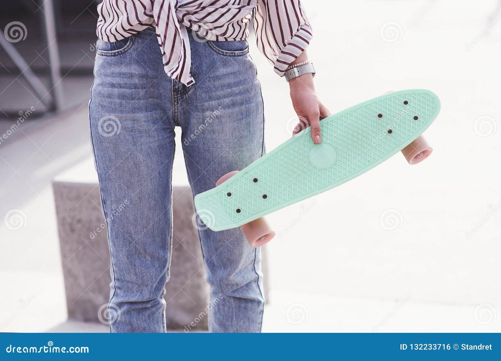 Skater fêmea adolescente bonito que senta-se na rampa no parque do patim Conceito de atividades urbanas do verão