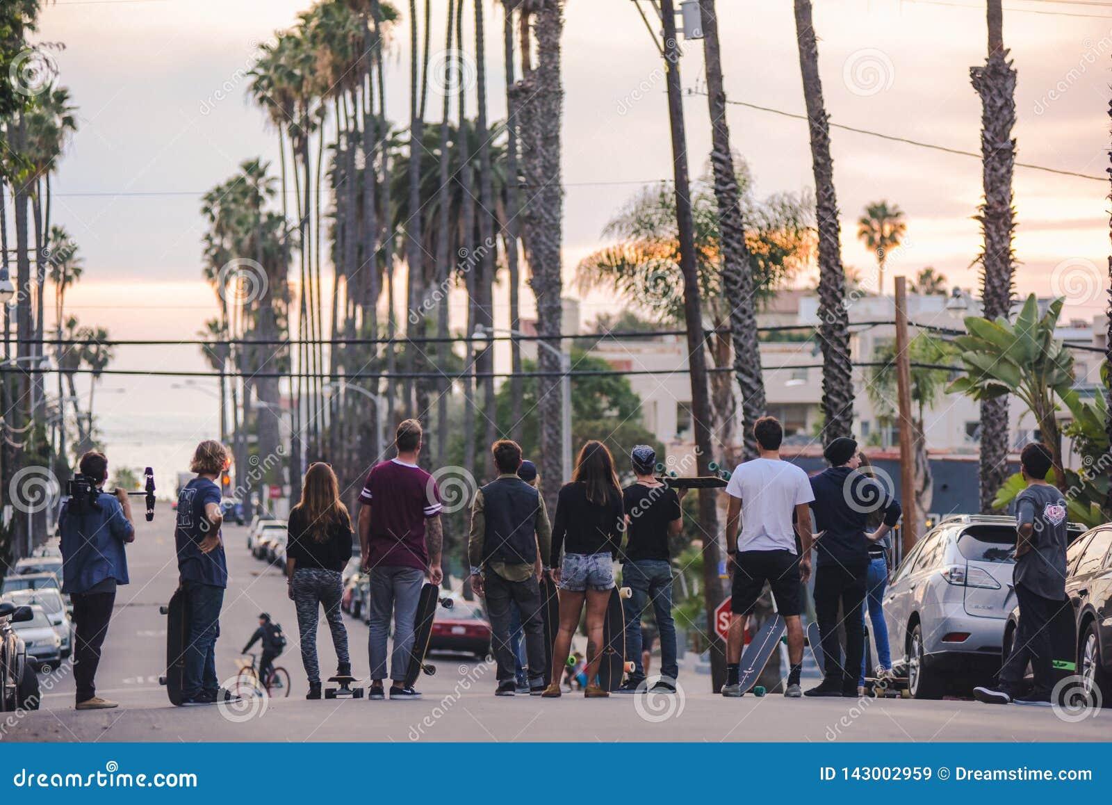 Skateres cerca de Venice Beach en la puesta del sol