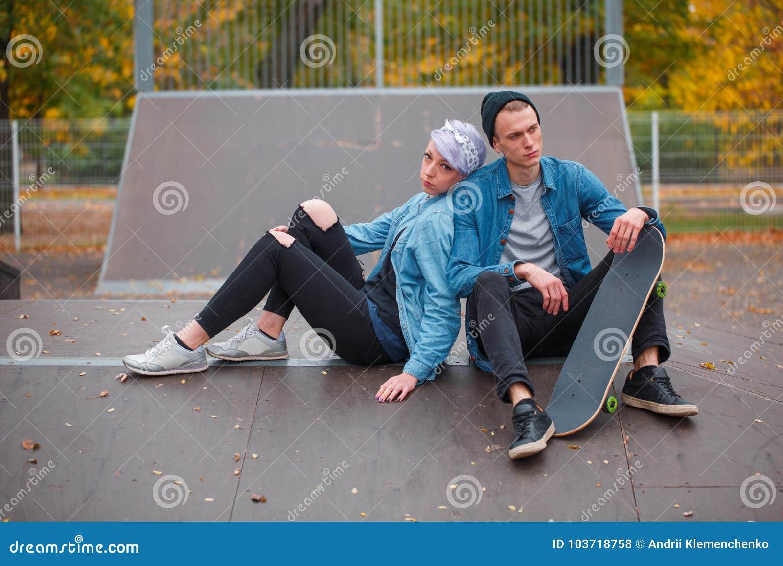 Skateres novos do indivíduo e da menina, fora em um dia brilhante do outono