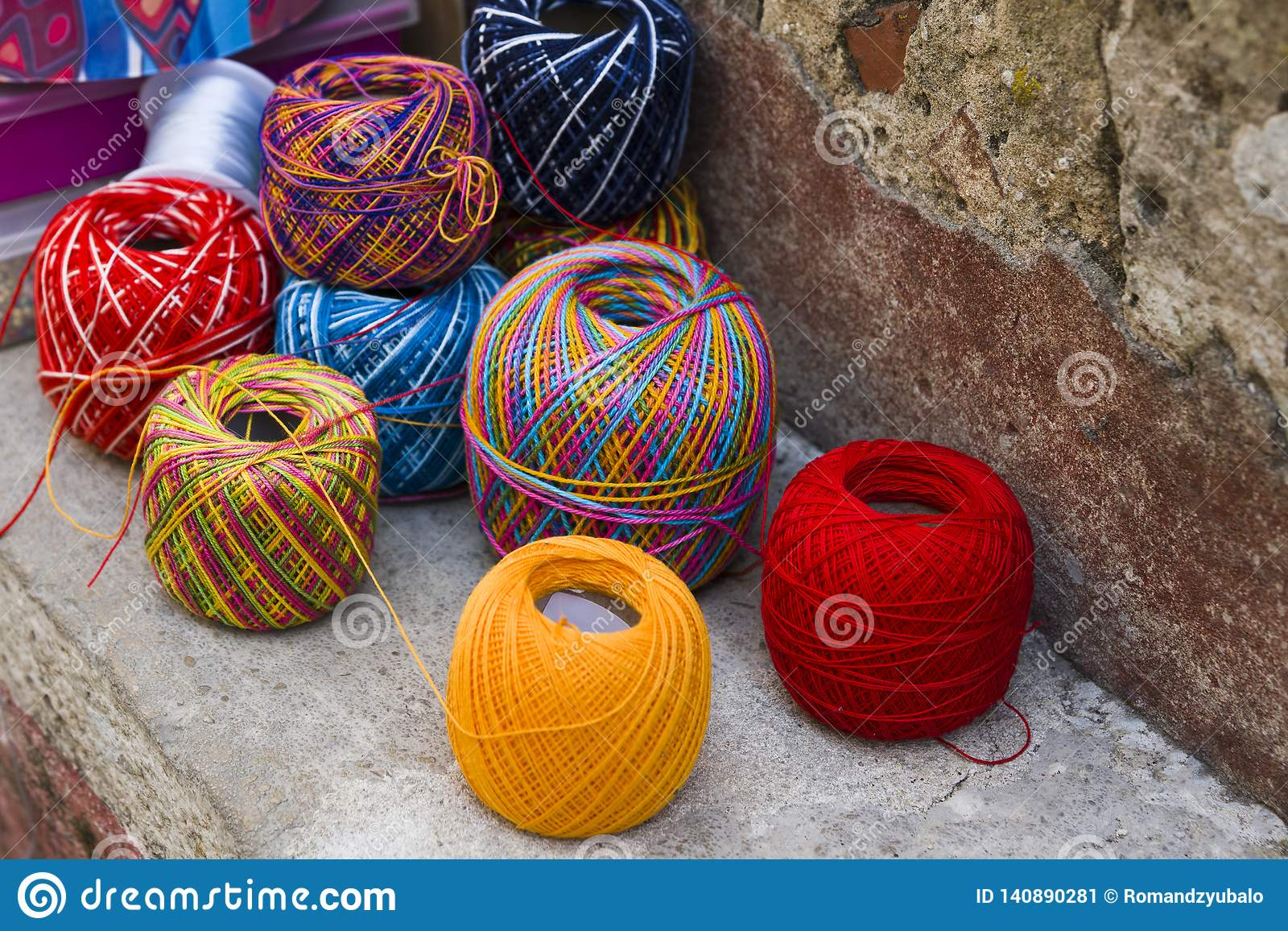 Skeins of bright colored wool lie on the stone border near the wall. In the background are boxes and a coil with a blue ribbon