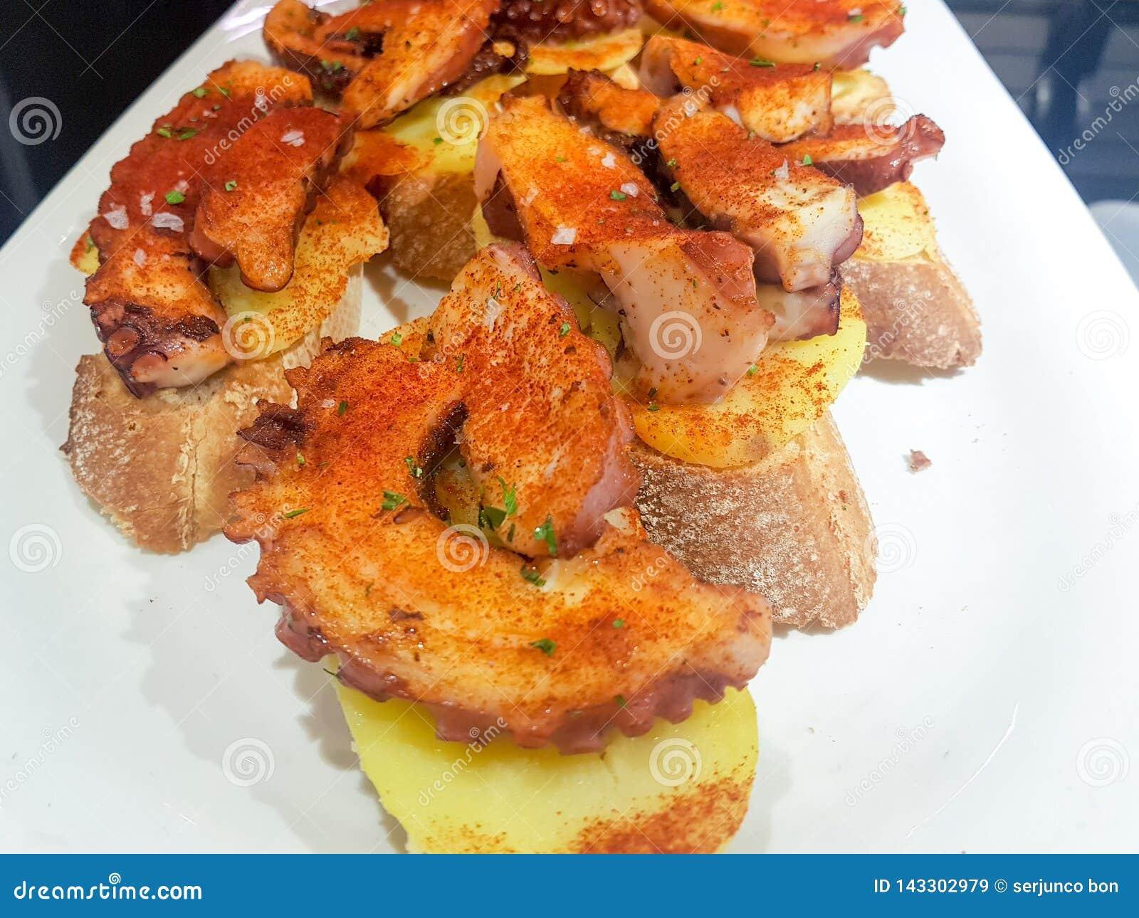 Skewer ośmiornicy na kawałku chleb w restauracyjnym barze
