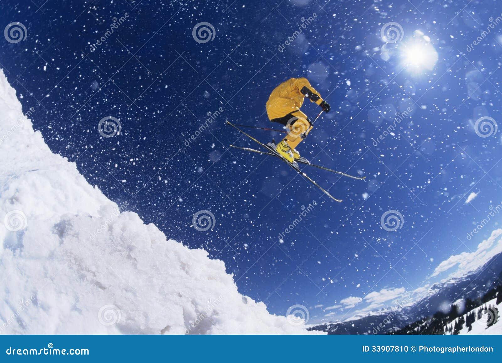 Skiër in midair boven sneeuw
