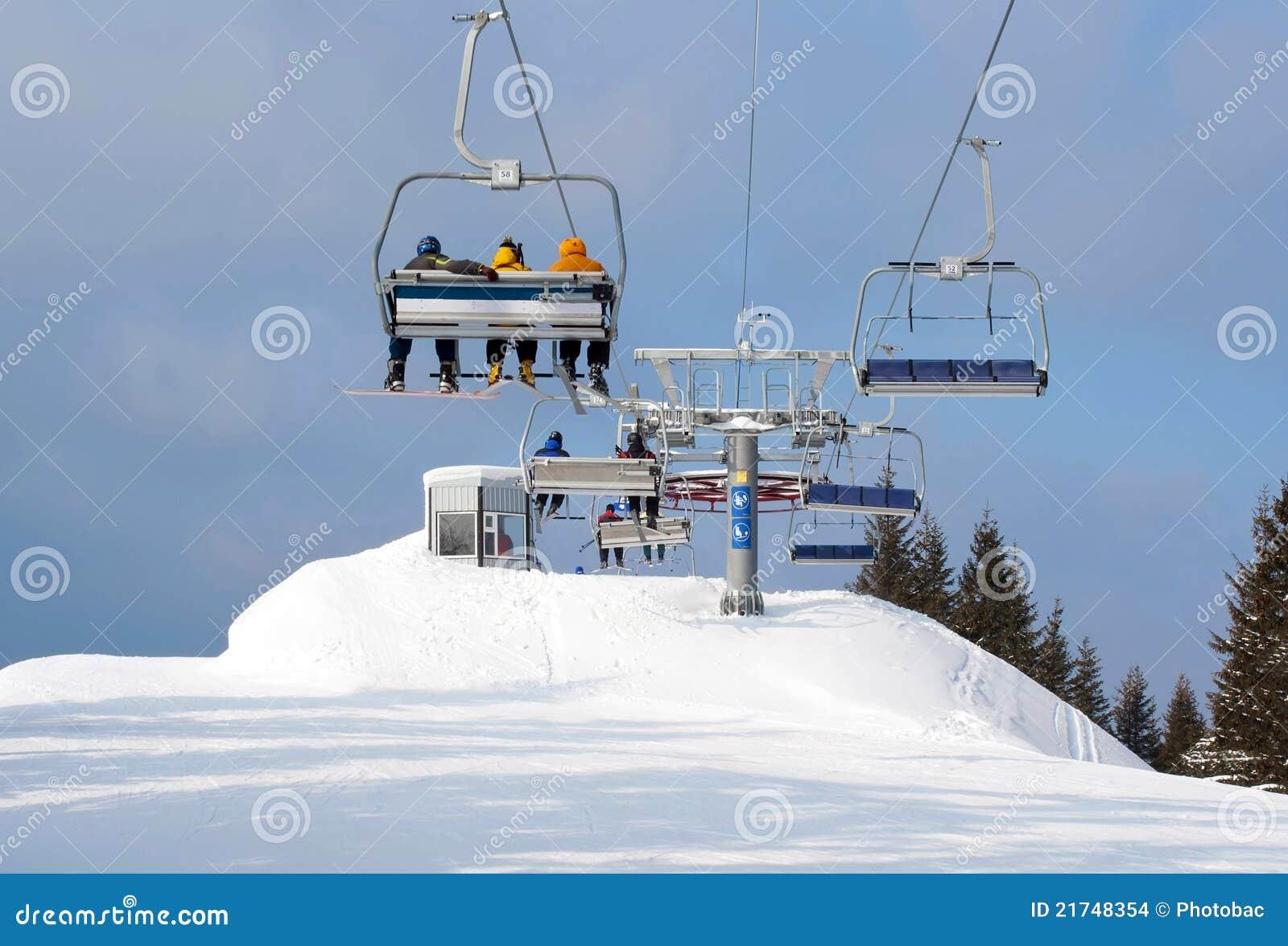 Skiërs die in stoeltjeslift tot bovenkant van berg aankomen