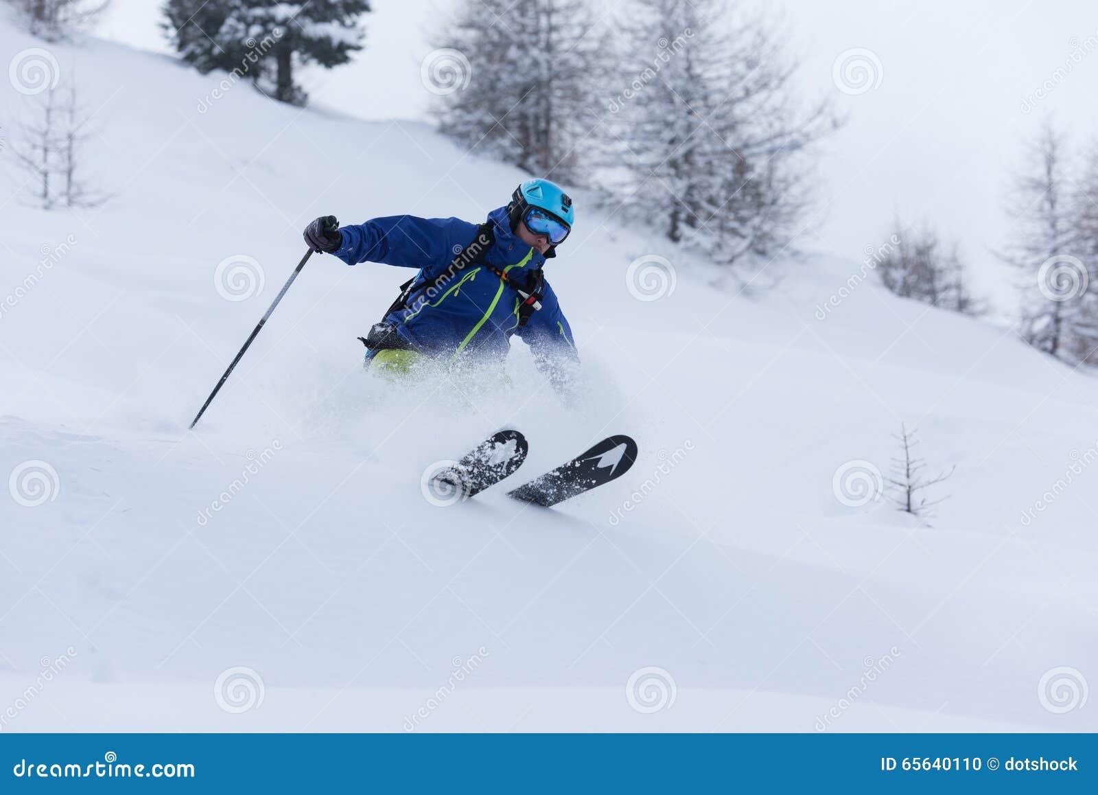 Ski de skieur de Freeride dans la neige profonde de poudre