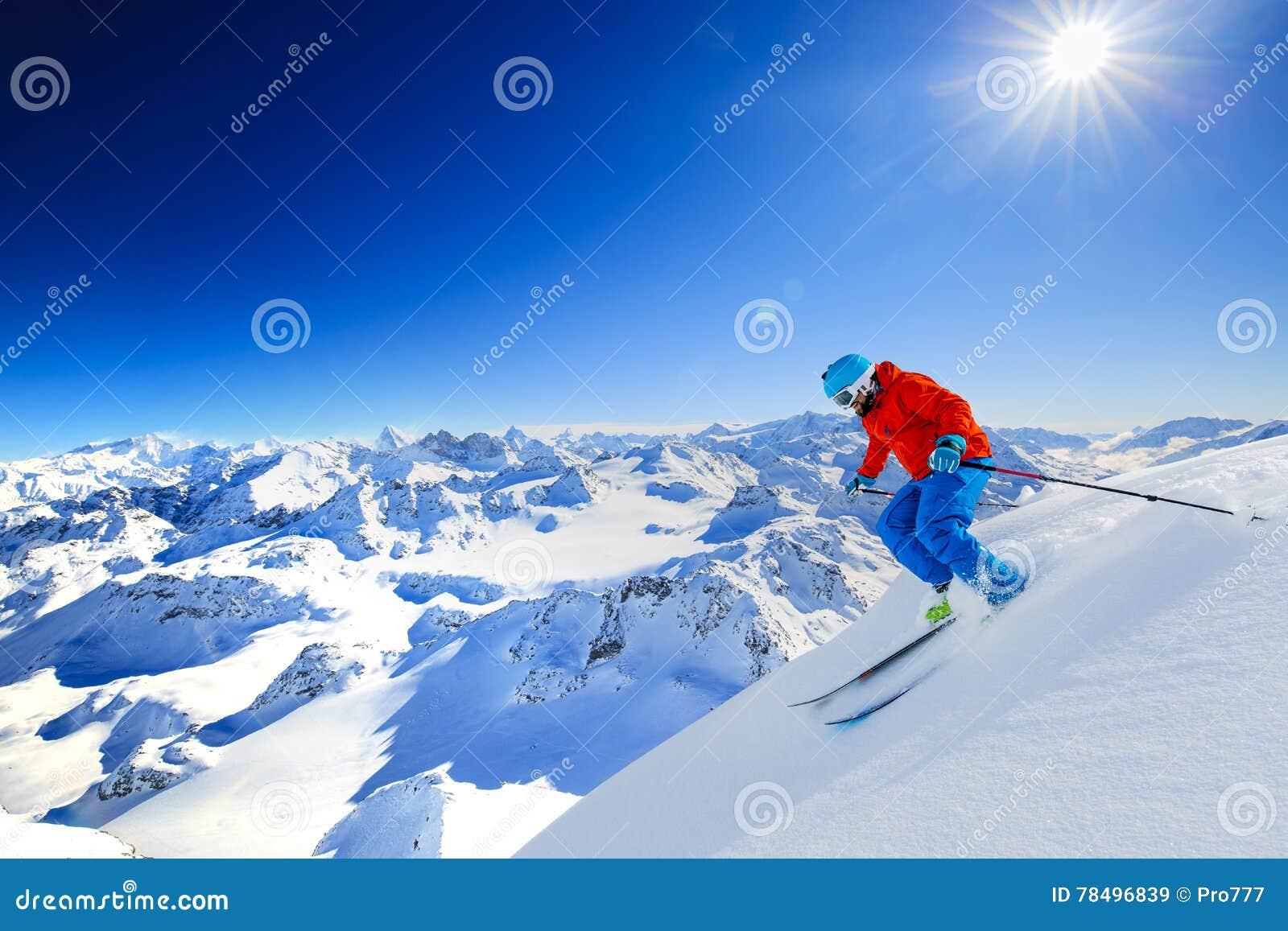Ski touring man reaching the top in Swiss Alps.