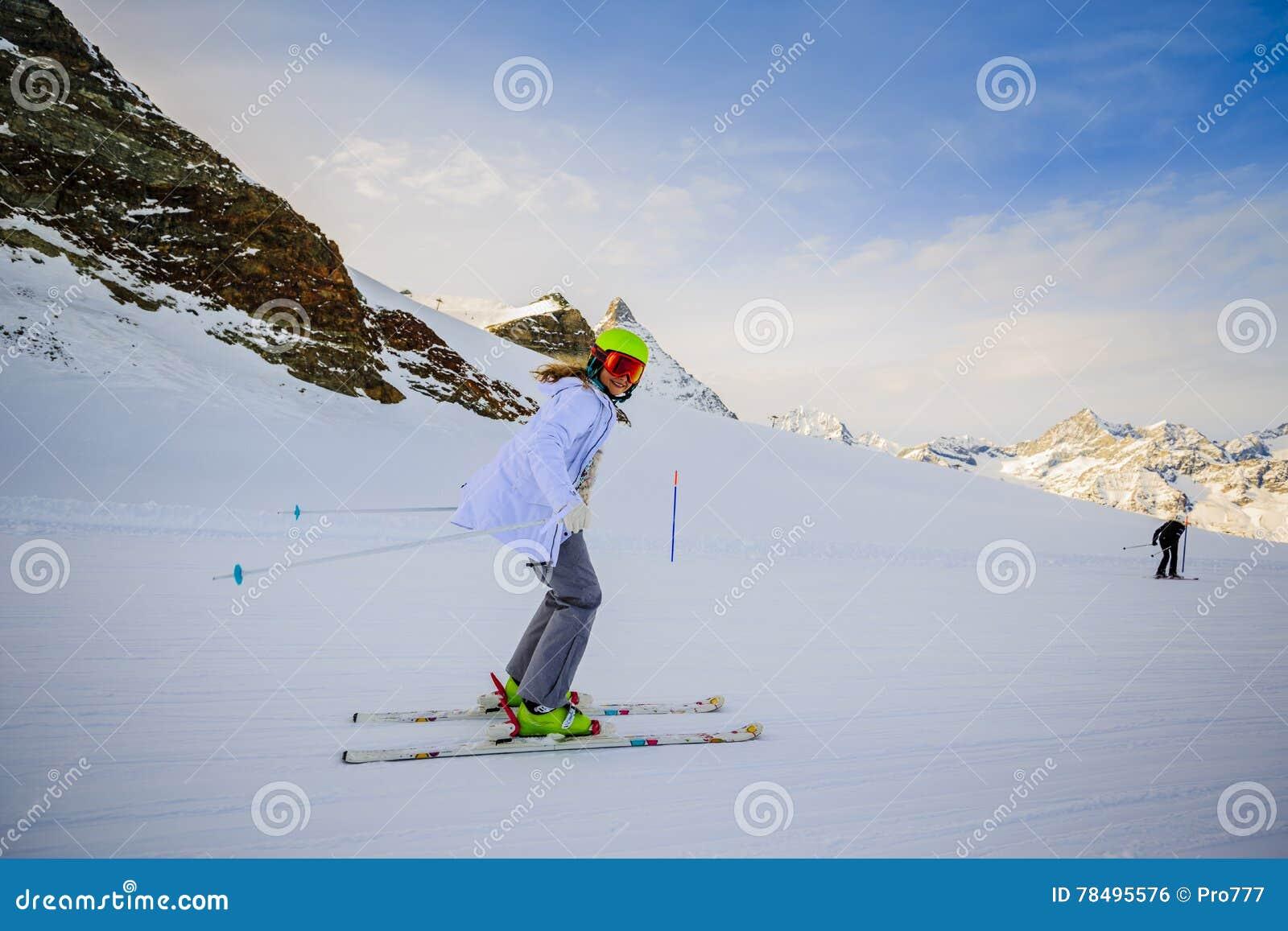 Skidåkning för tonårs- flicka i schweiziska fjällängar i Sunny Day