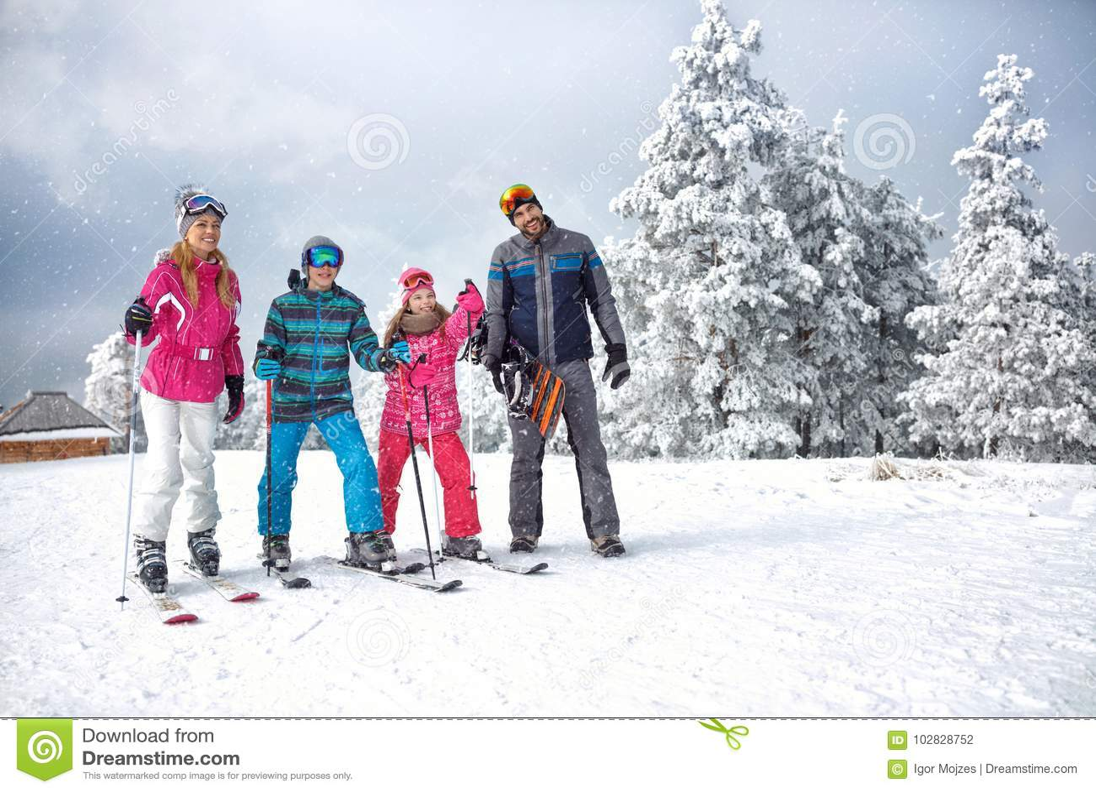 Skidåkningfamilj som tycker om vintersemester på insnöad solig kall dag