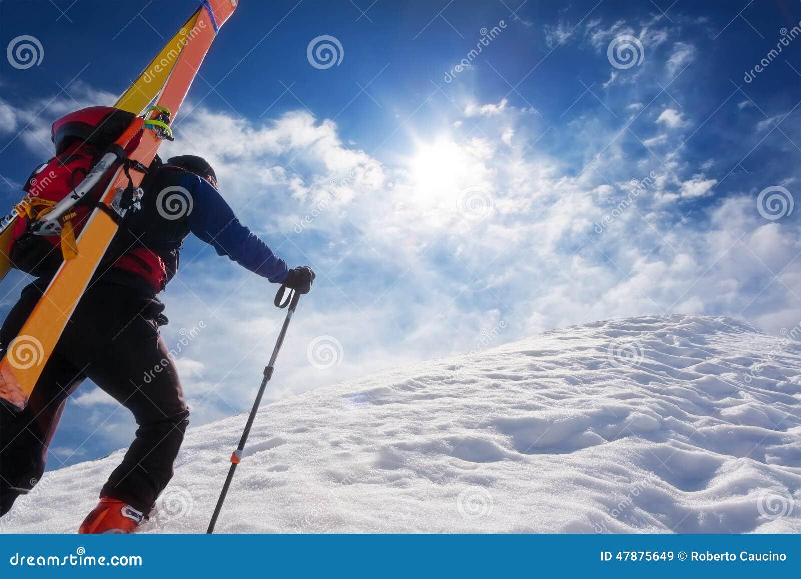 Skidar bergsbestigaren som går upp längs en brant snöig kant med set