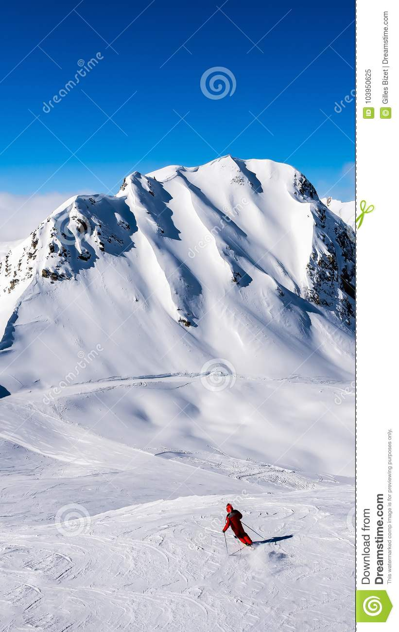 A skier alone on the ski slopes with blue sky