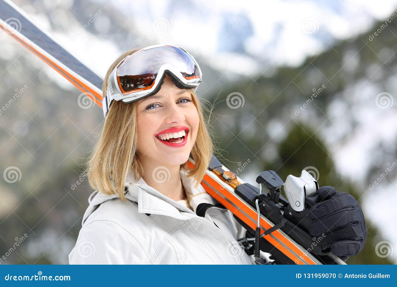 Skieur heureux regardant la caméra tenant des skis