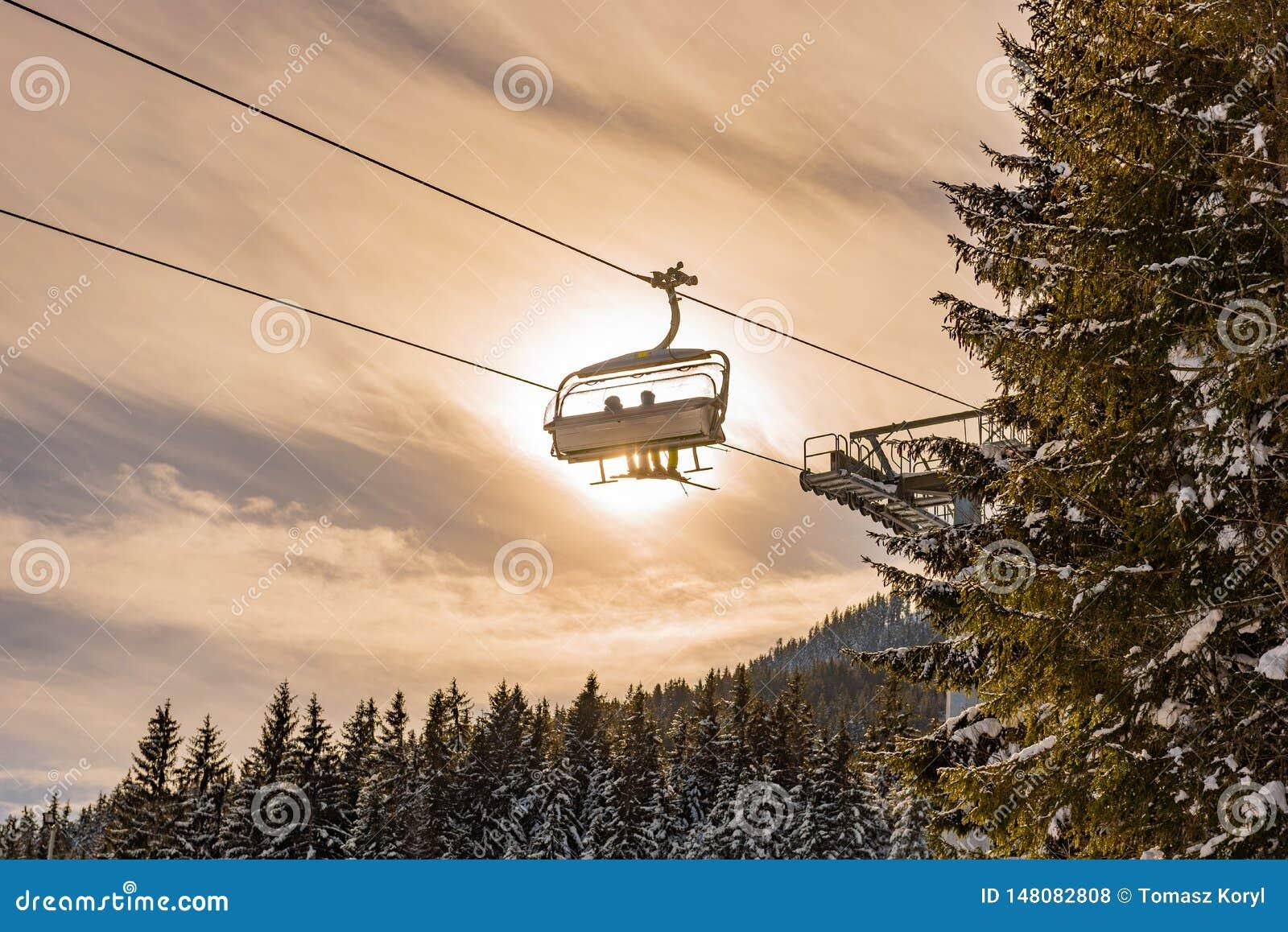 Skieurs sur le t?l?si?ge de ski sur le le fond du soleil et d un ciel bleu