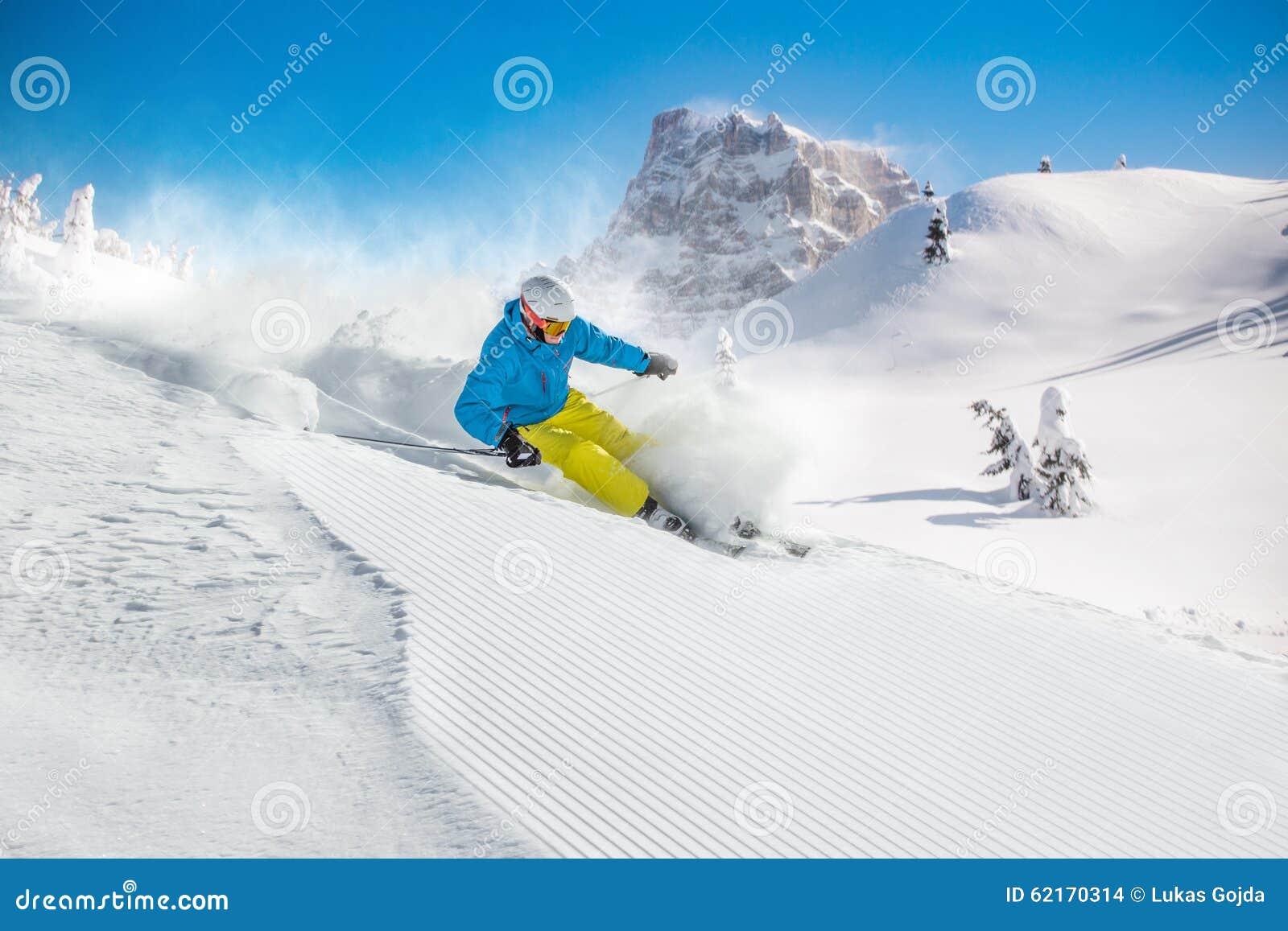 Skifahrer, der abwärts im Hochgebirge Ski fährt