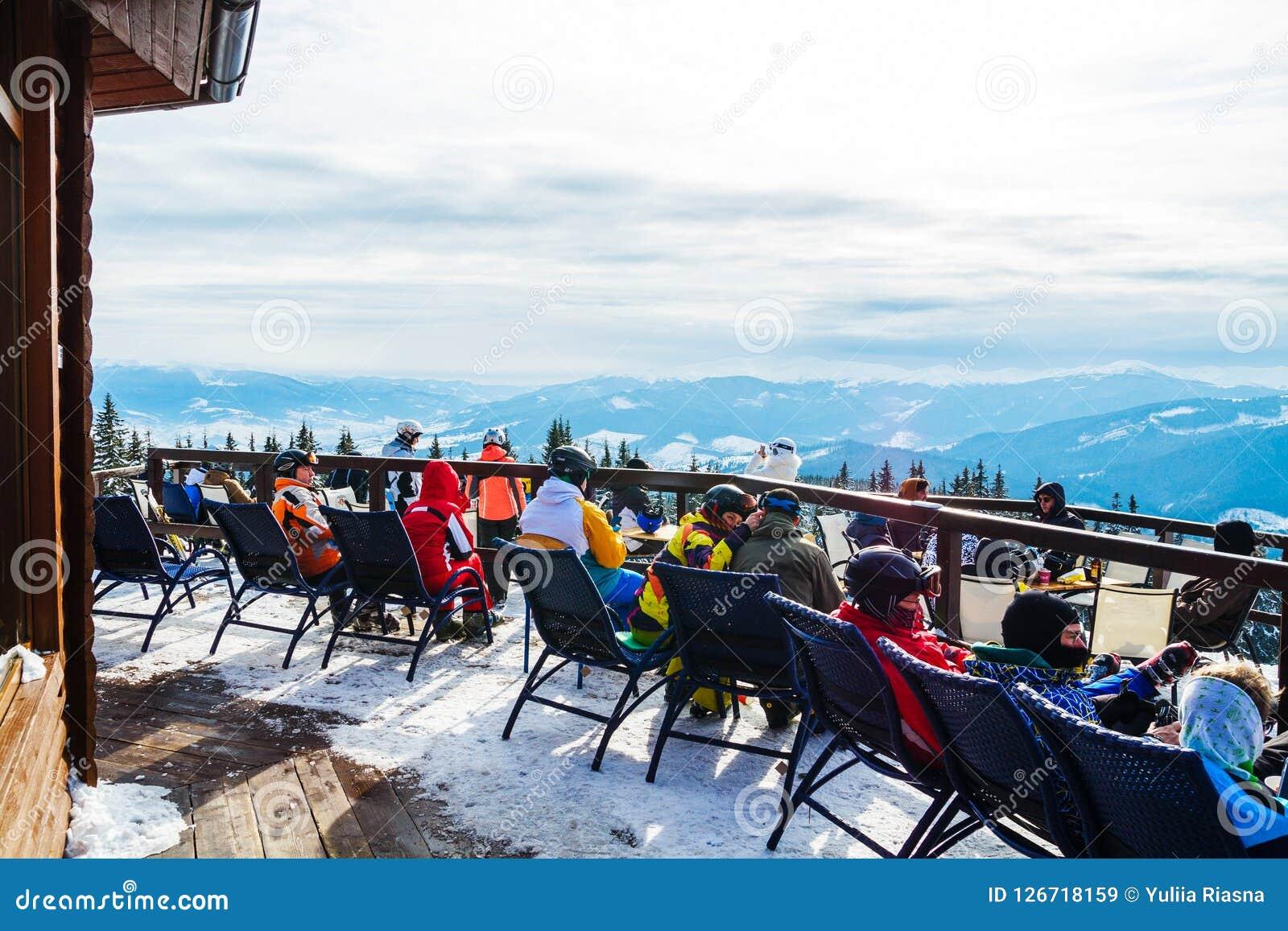 Skifahrer sitzen auf Stühlen nahe einem Restaurant auf einen Berg Leute im Skianzugrest und -getränk