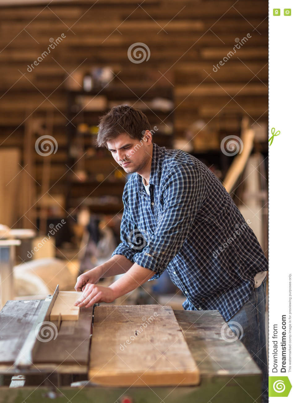 Skilled carpenter working in his woodwork workshop, using a circular saw