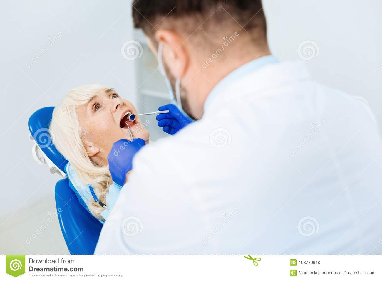 Skilled dentist examining the patient