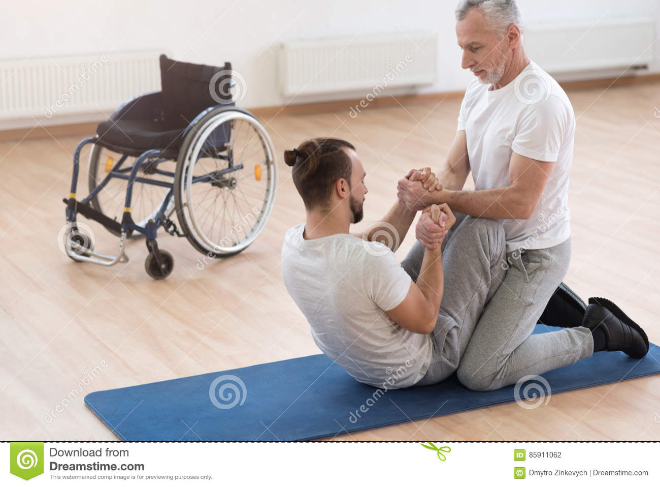 Skilled orthopedist assisting the disabled in the gym stock photo