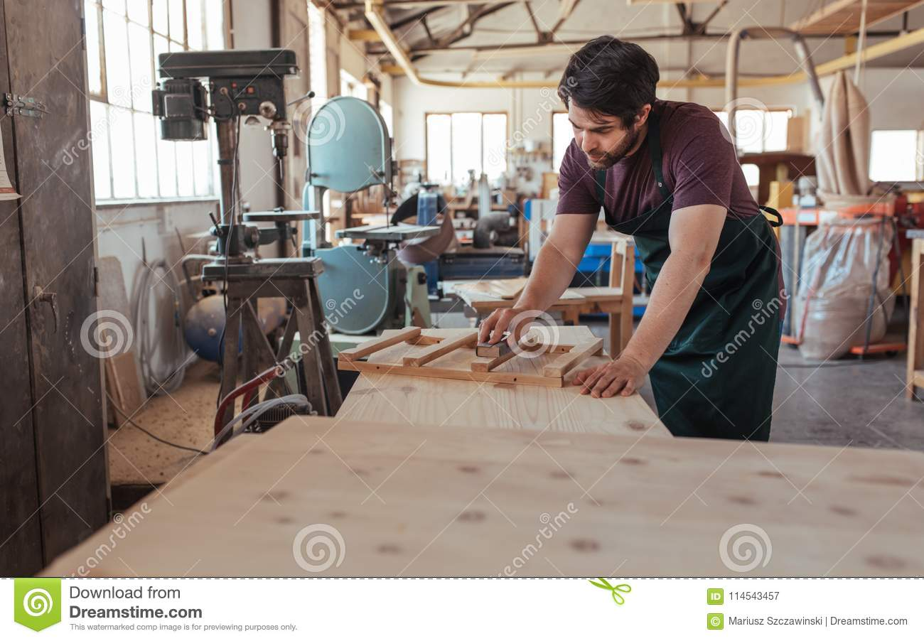 Skilled Young Carpenter Sanding Wood In His Large Workshop Stock
