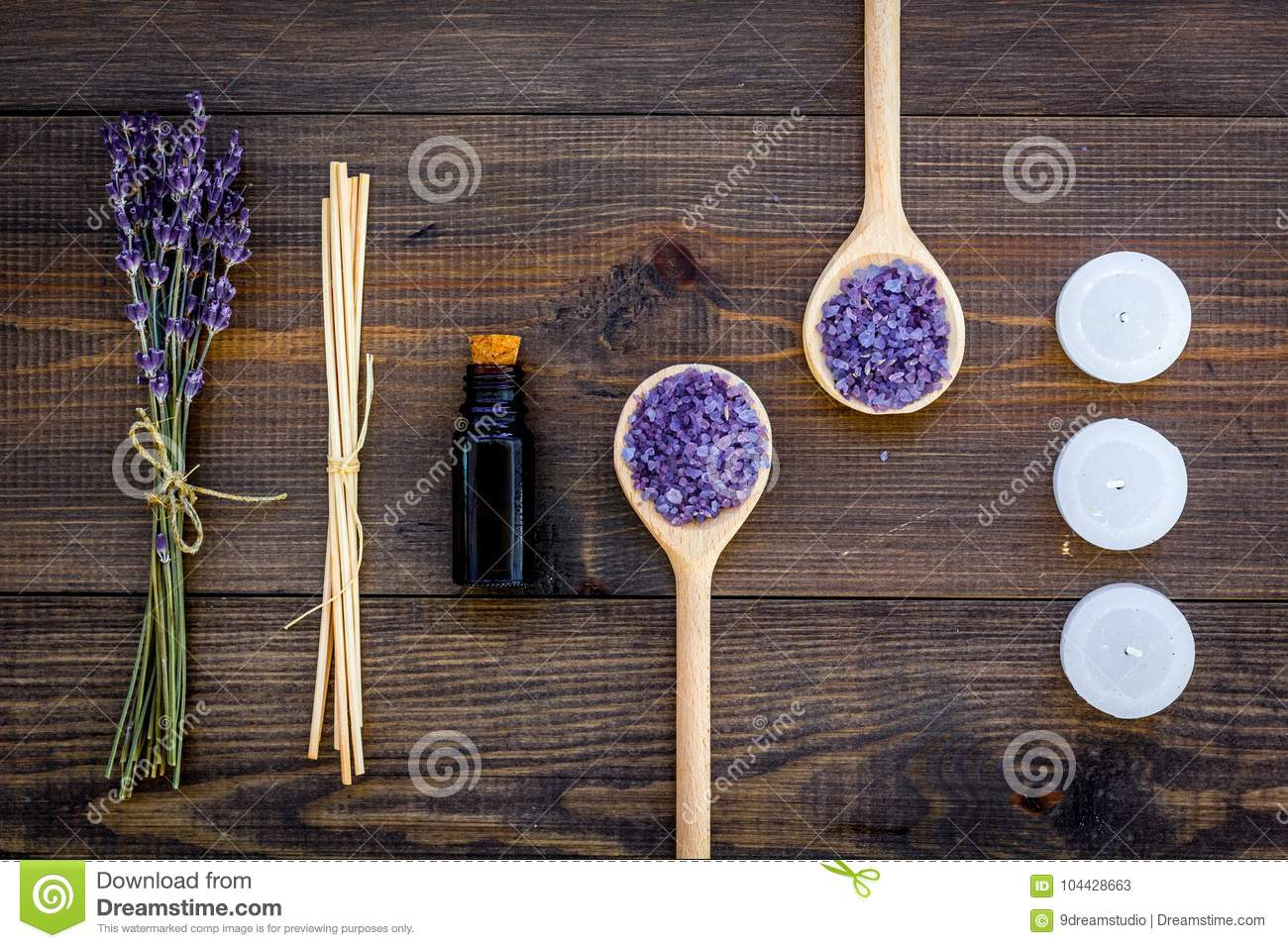 Skin care and relax. Cosmetics and aromatherapy concept. Lavender spa salt and oil on dark wooden background top view