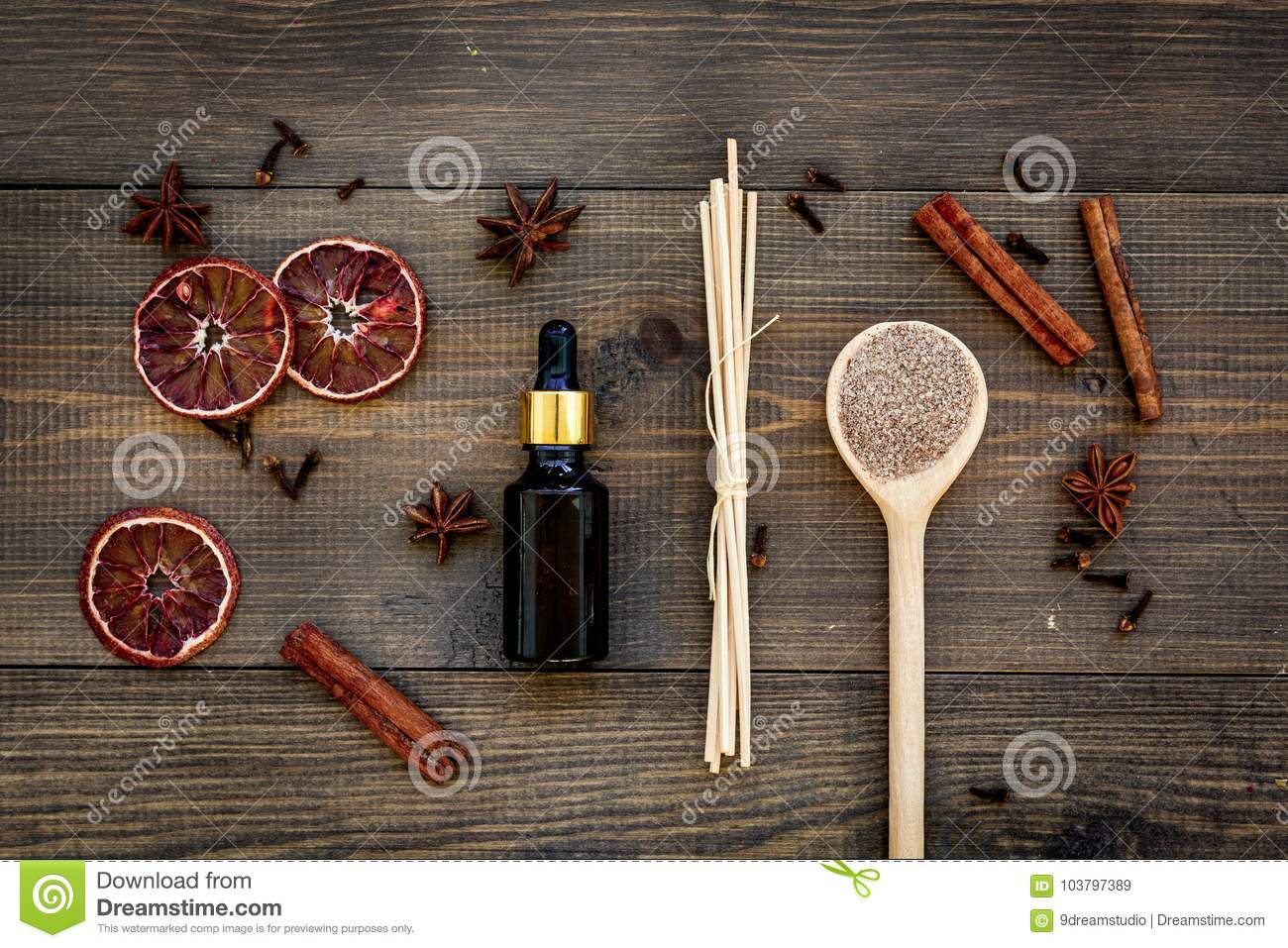 Skin care and relax. Cosmetics and aromatherapy concept. Spa salt and oil with spices cinnamon on dark wooden background