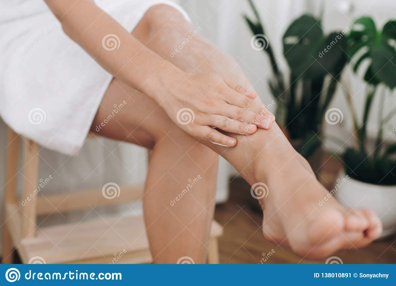 Skin care and wellness concept. Girl hand with moisturizer cream smearing legs for soft skin result. Young woman applying cream on