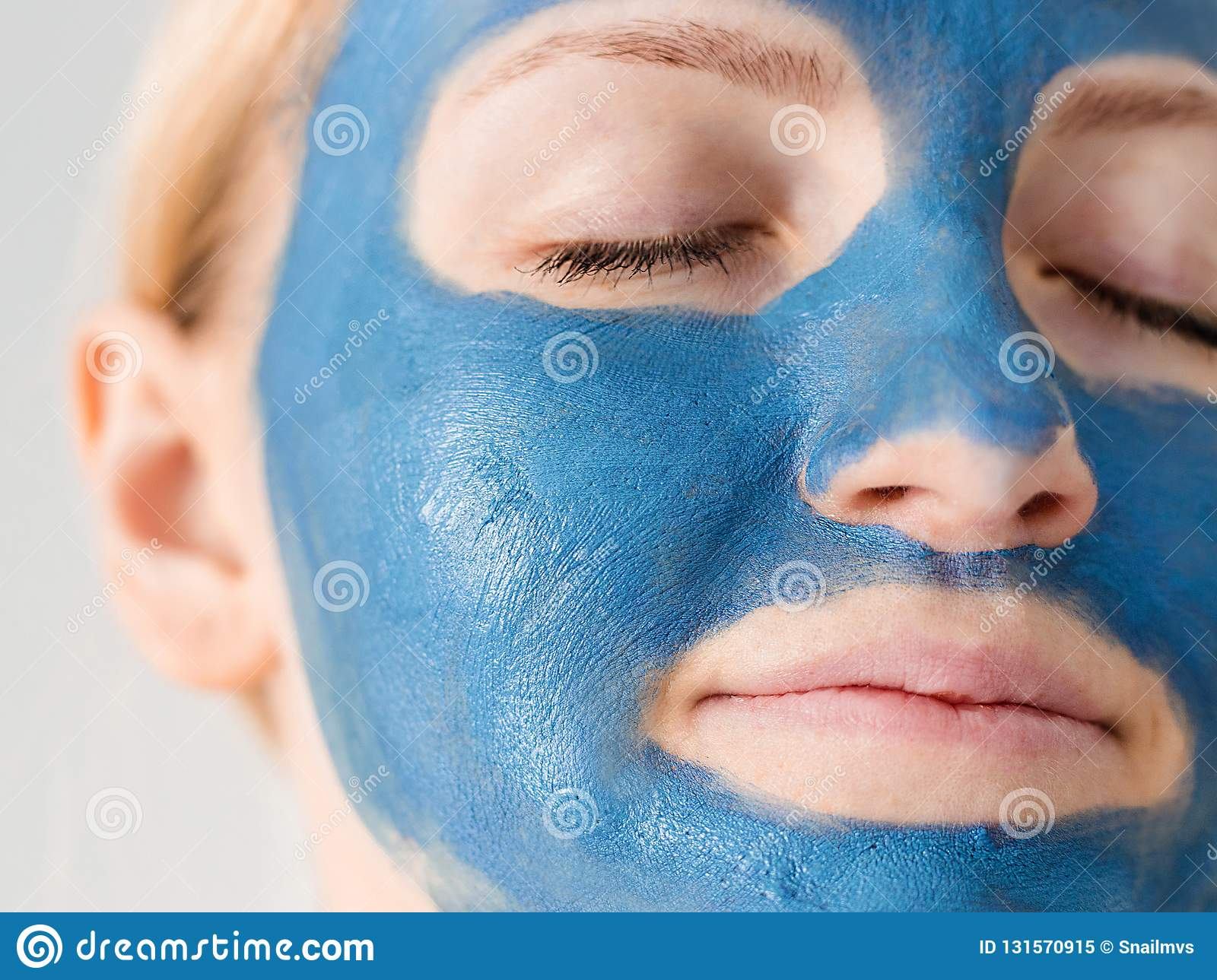 Skin care. Woman face with blue clay mud mask close up. Girl taking care of oily complexion. Beauty treatment.