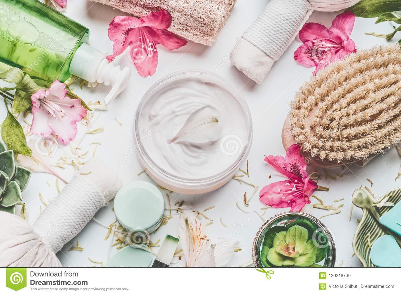 Skin cream with flowers petals and others body care cosmetic products and accessories on white background