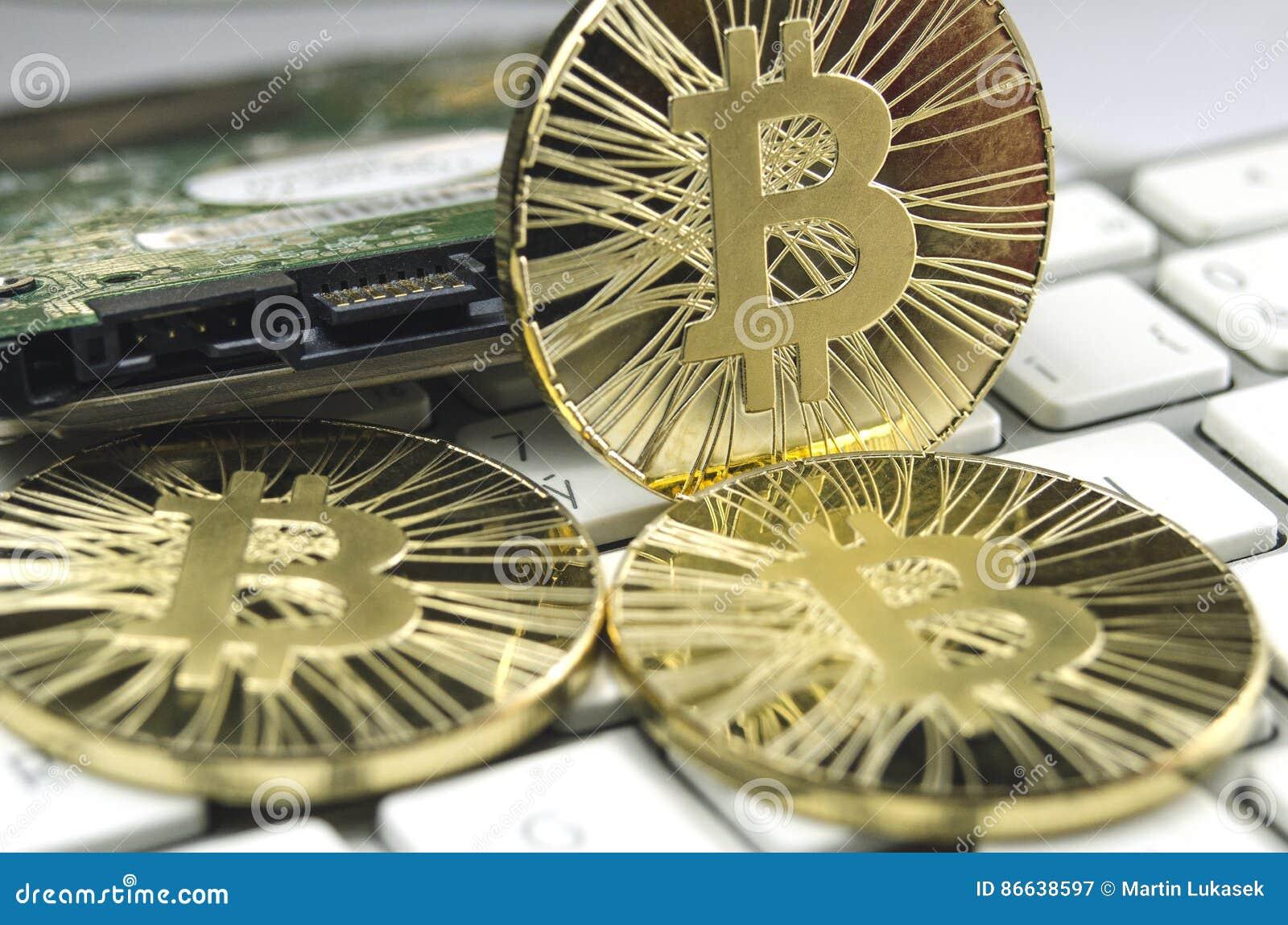 Skinande guld- Bitcoin mynt som lägger på det vita tangentbordet