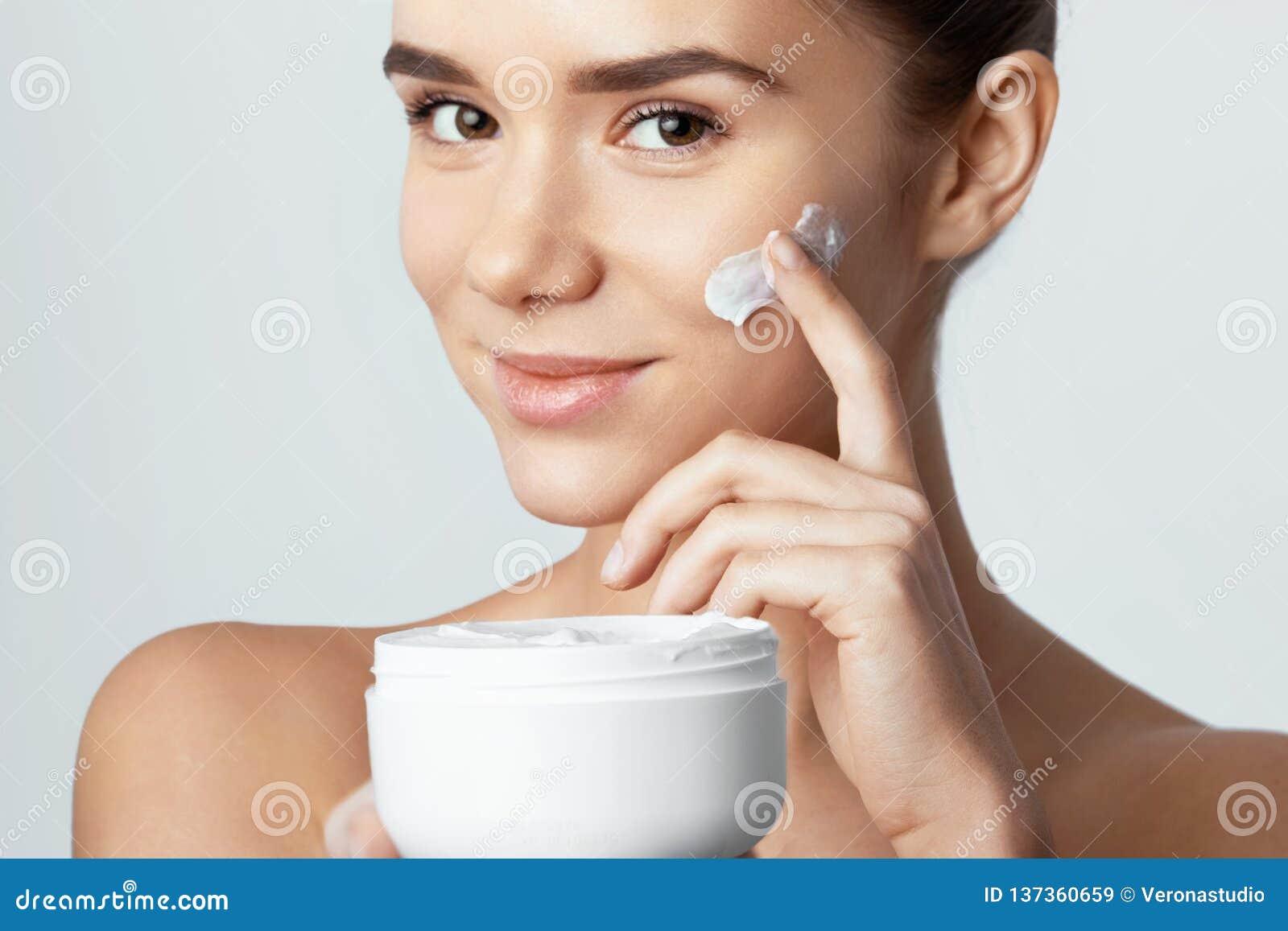 Skincare Concepto de la belleza Mujer bonita joven que sostiene la crema cosmética