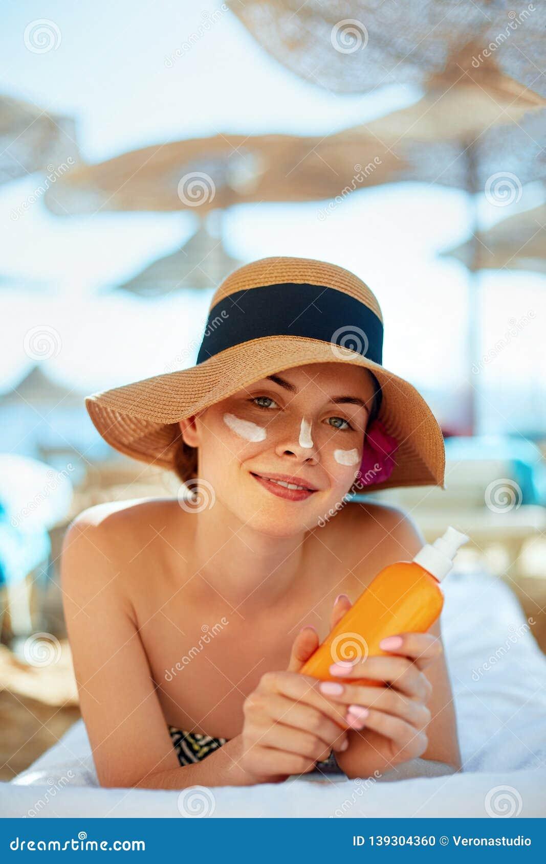 Skincare Concetto di bellezza Giovane crema graziosa del sole della tenuta della donna ed applicarsi sul suo fronte