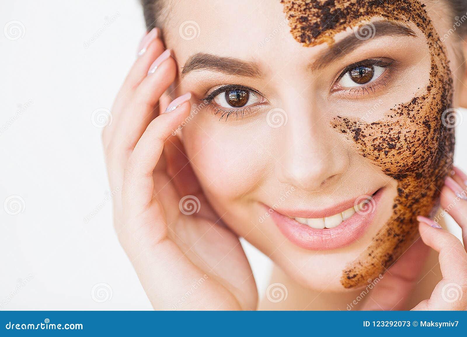 Skincare del fronte La giovane ragazza affascinante fa una maschera nera o del carbone