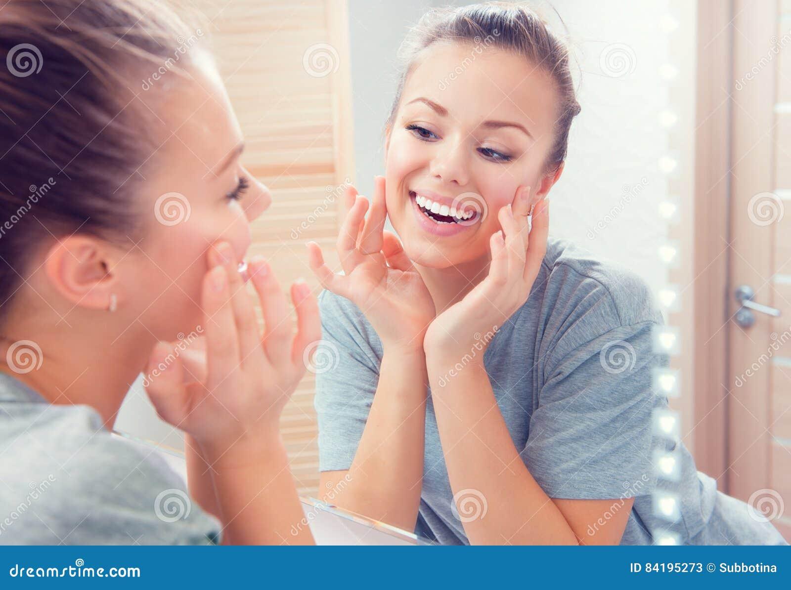 Skincare Ung härlig tonårs- flicka som trycker på hennes framsida