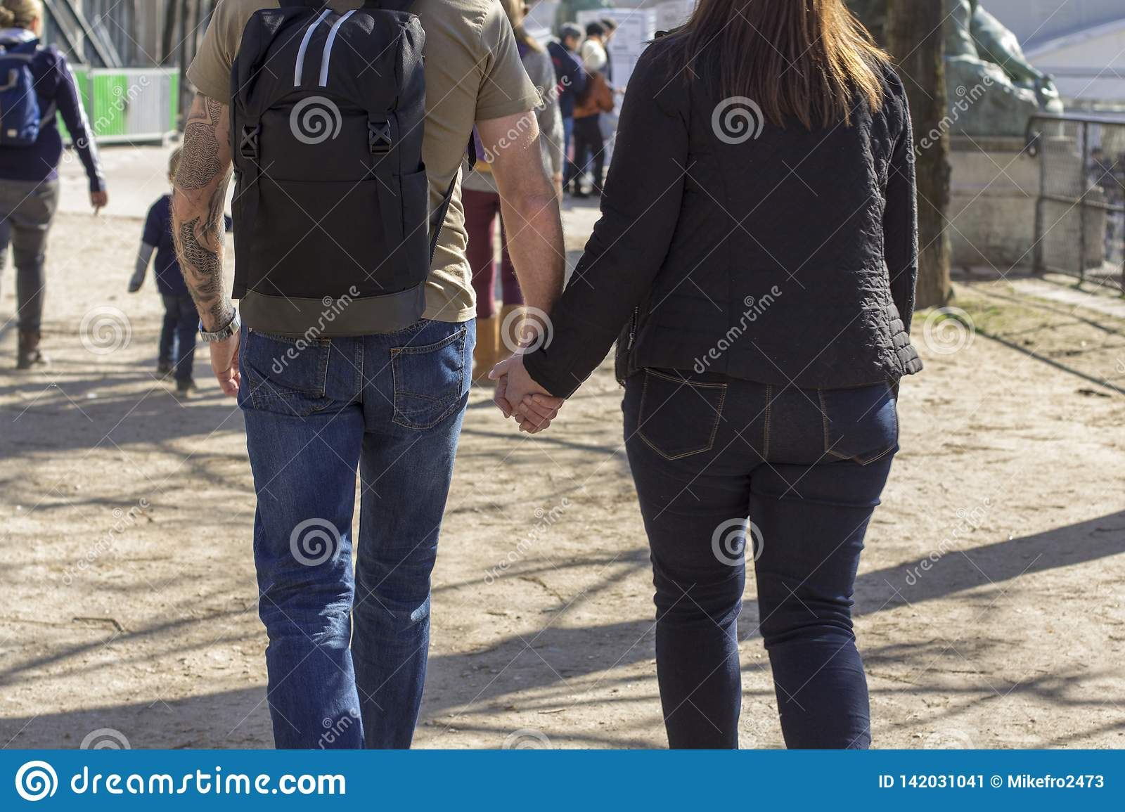 Skinny man holds the hand of a woman while walking